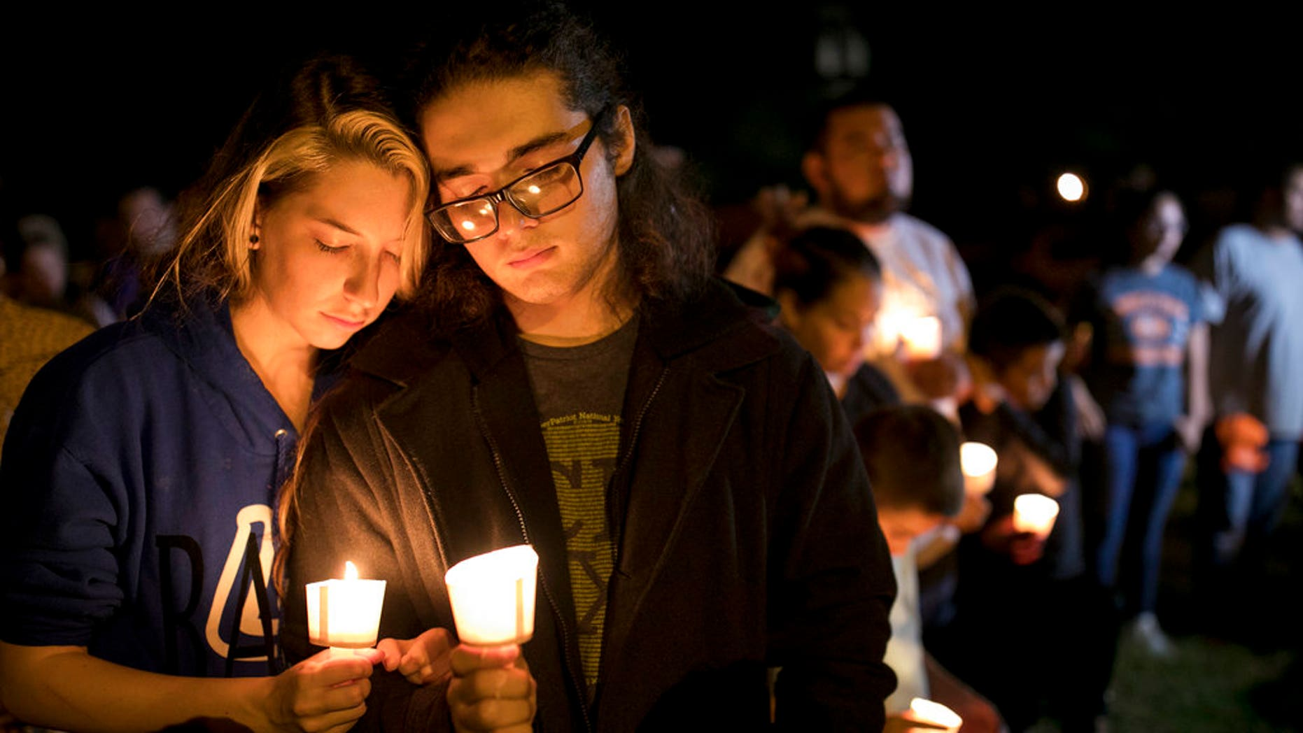 Bailey LeJeaune, 17, and David Betancourt, 18, hold candles during a vigil in Sutherland Springs for the victims of a deadly shooting at the First Baptist Church in Sutherland Springs, Texas, Sunday, Nov. 5, 2017. A man opened fire inside of the church in the small South Texas community on Sunday, killing more than 20 people. (Jay Janner/Austin American-Statesman via AP)