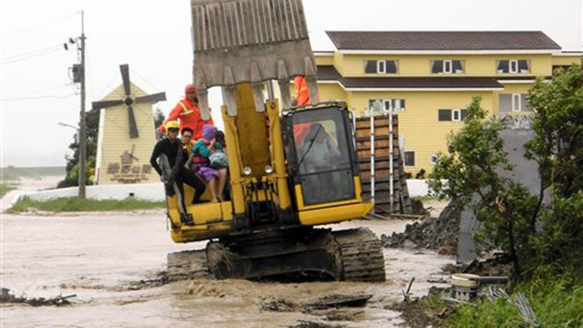 In this photo released by Hengchun Township Fire Department, residents are evacuated on an excavator as Typhoon Nanmadol began blowing toward Taiwan in Hengchu township, Pingtung county, southern Taiwan, Sunday, Aug. 28, 2011.