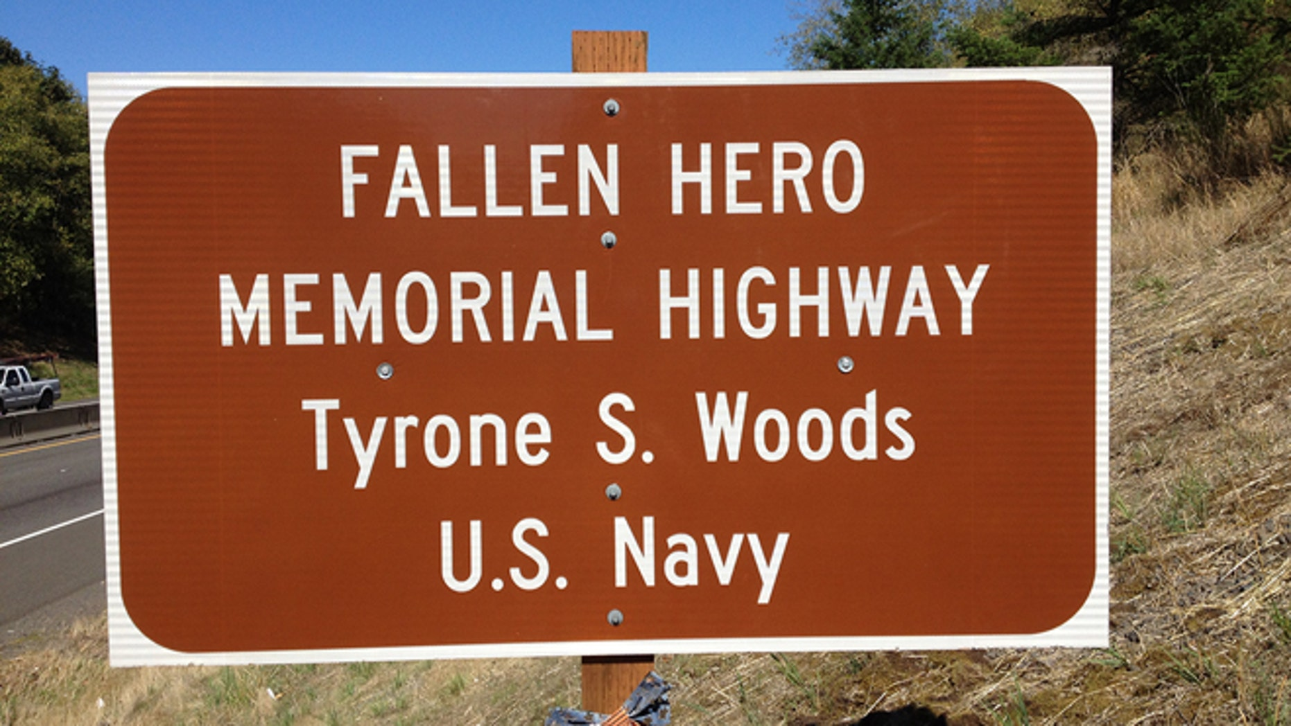 An Oregon sign reflects a stretch of highway dedicated in memory of Tyrone Woods, who was killed in the 2012 Benghazi attack.