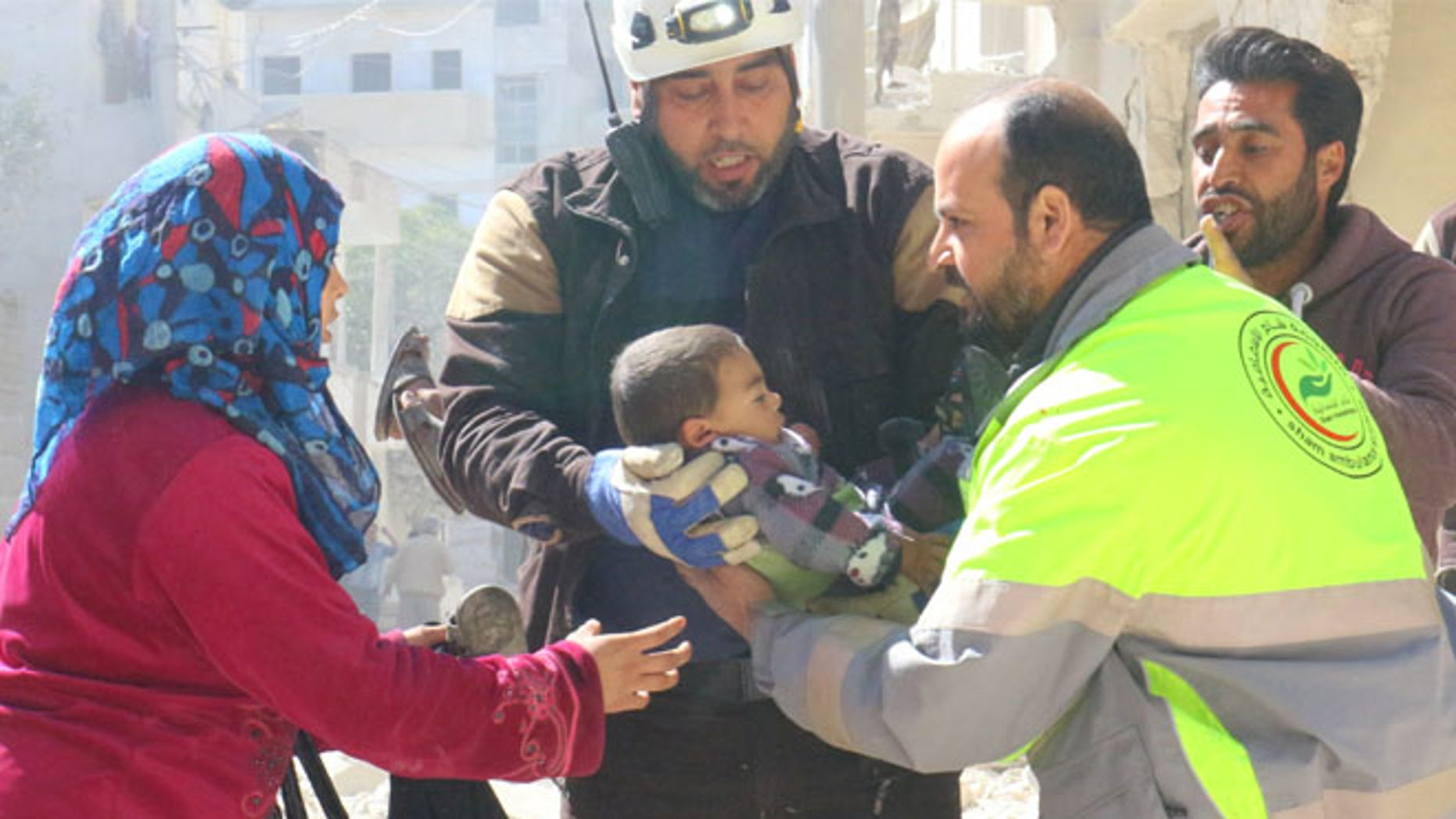 MARCH 19: People and a civil defence personnel carry a child who survived after an airstrike on rebel-held Idlib city.
