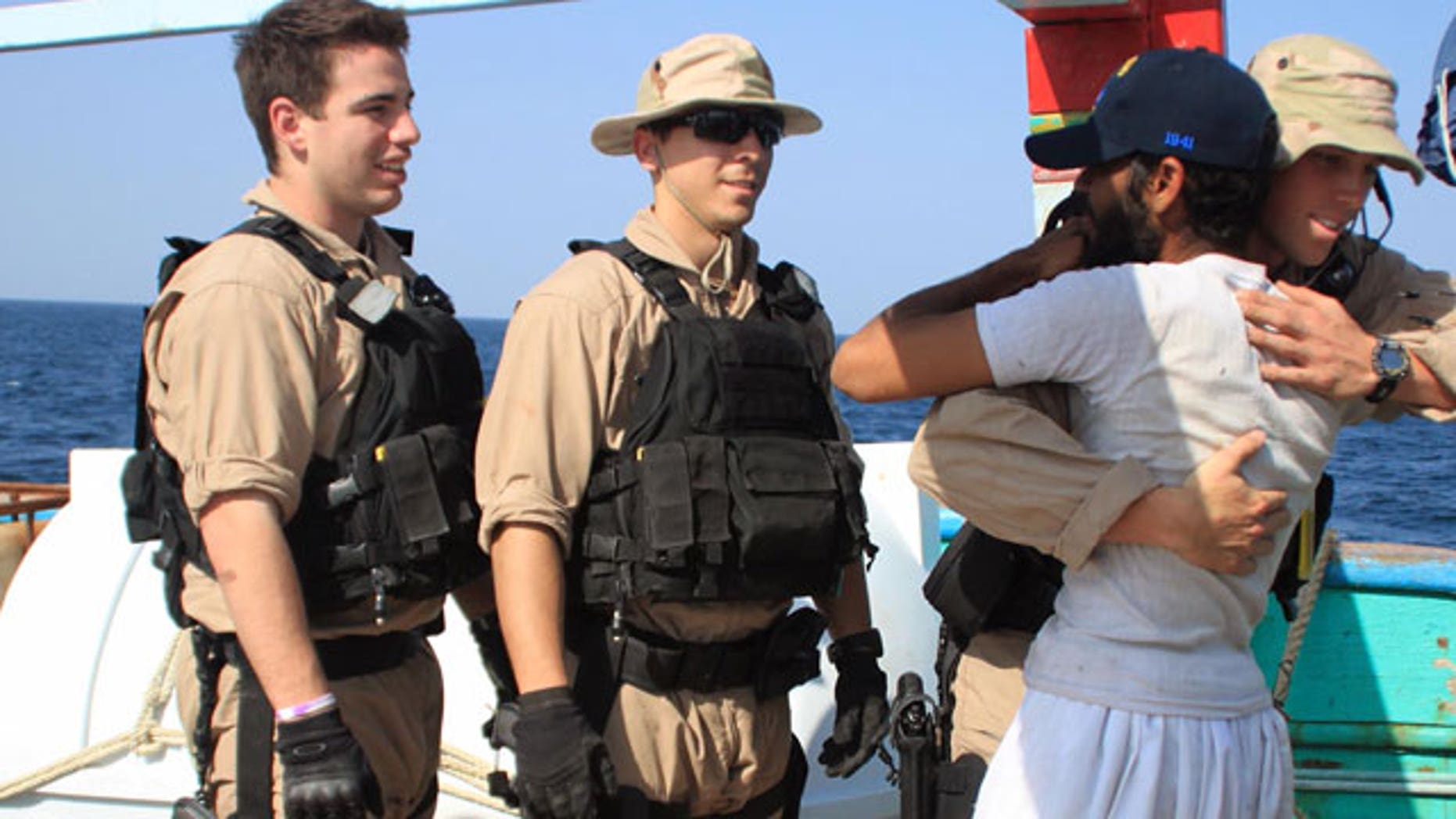 January 6, 2012: U.S. Navy sailors assigned to the guided-missile destroyer USS Kidd greet a crew member of the Iranian fishing vessel, the Al Molai Fin the Arabian Sea.