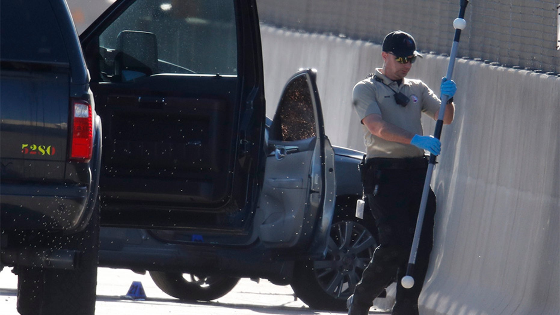 June 1, 2018: A Denver Police Department technician investigates the scene where a Nissan sedan, background center, being driven by an Uber driver crashed into a retaining wall along Interstate 25 south of downtown Denver early Friday.