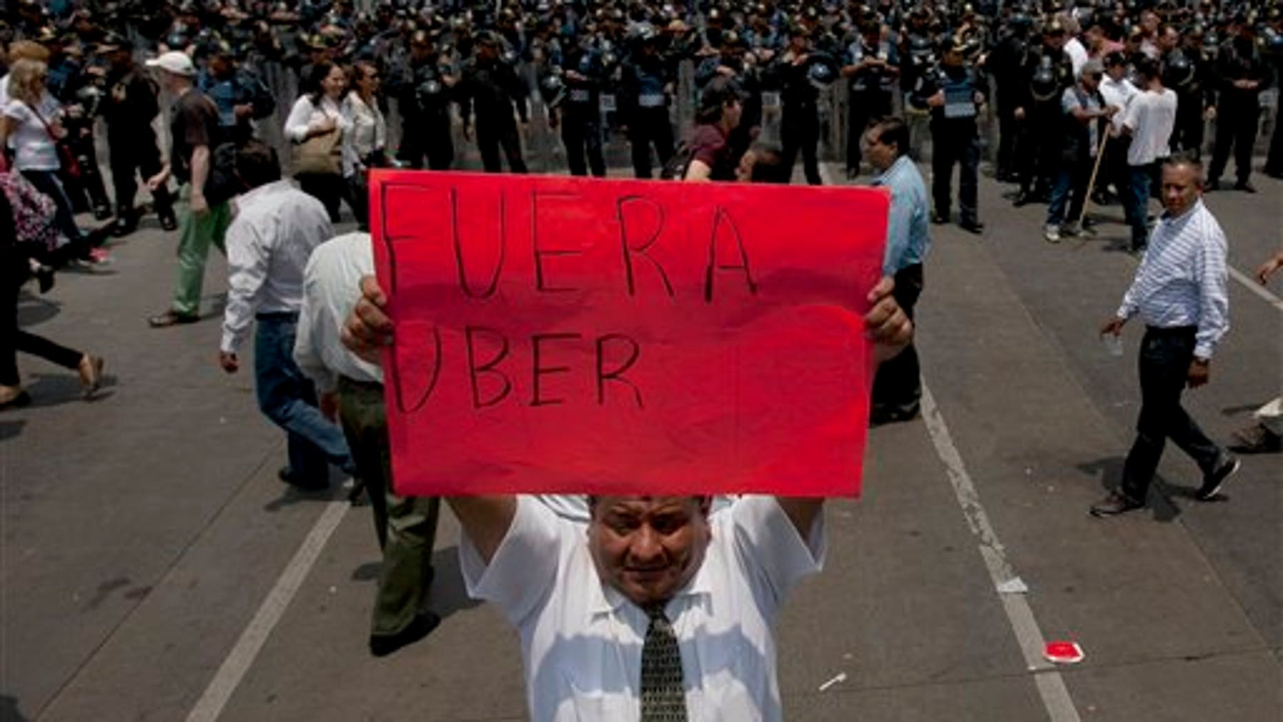 """A man holds a sign the reads in Spanish """"Uber Out"""" in front of a phalanx of riot police as thousands of taxi drivers blocked the main streets in Mexico City, Monday, May 25, 2015. The Mexican taxi drivers' union called for a protest against unlicensed and UBER taxis working in Mexico City. (AP Photo/Marco Ugarte)"""
