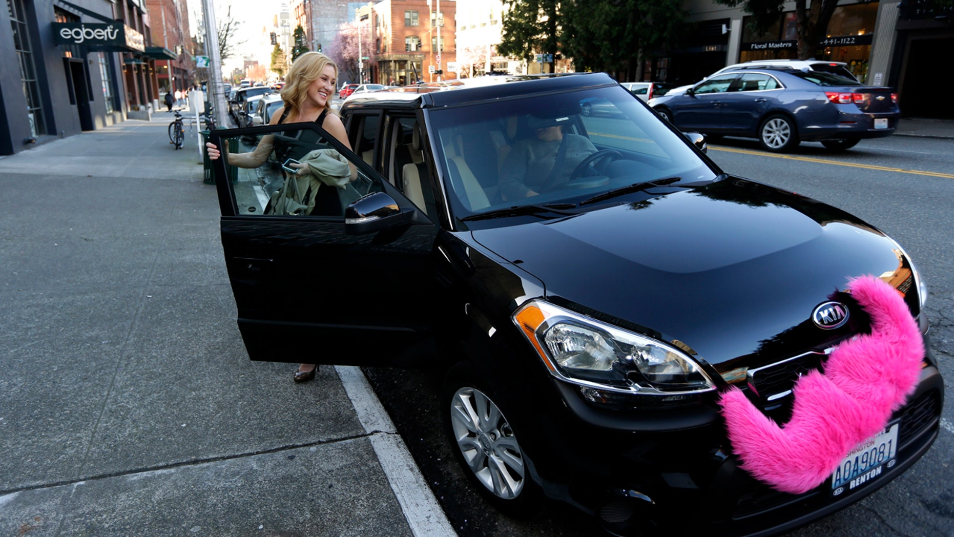 FILE - In this March 12, 2014 file photo, Katie Baranyuk gets out of a car driven by Dara Jenkins, a driver for the ride-sharing service Lyft, after getting a ride to downtown Seattle. Seattle may soon become the first city to let drivers of ride-hailing companies such as Uber and Lyft collectively bargain over pay and working conditions. (AP Photo/Ted S. Warren, File)
