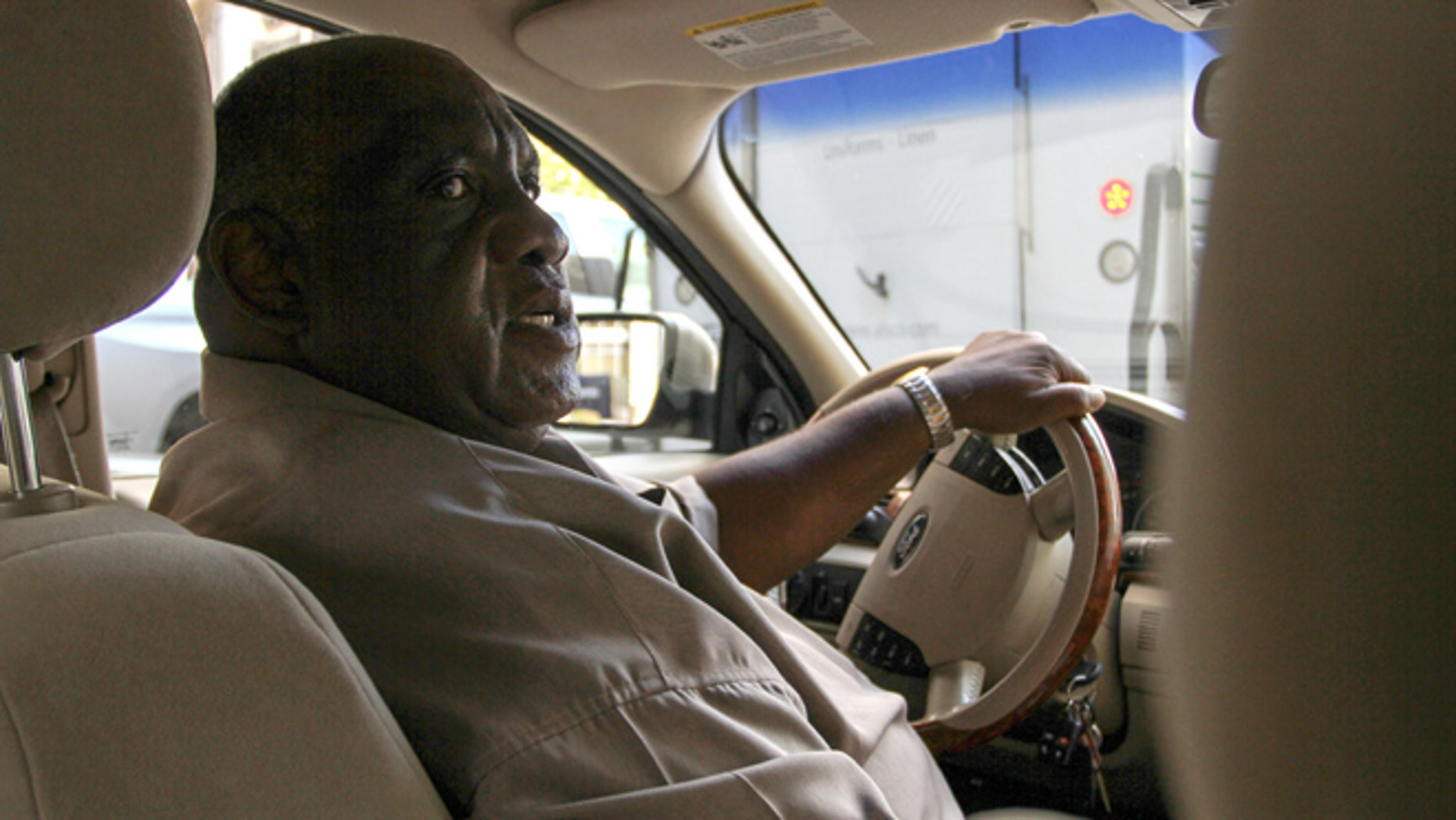 Retired bus driver Ellis Hill drives the car he uses as an Uber driver Thursday, Aug. 11, 2016, in Philadelphia. (AP Photo/Dake Kang)