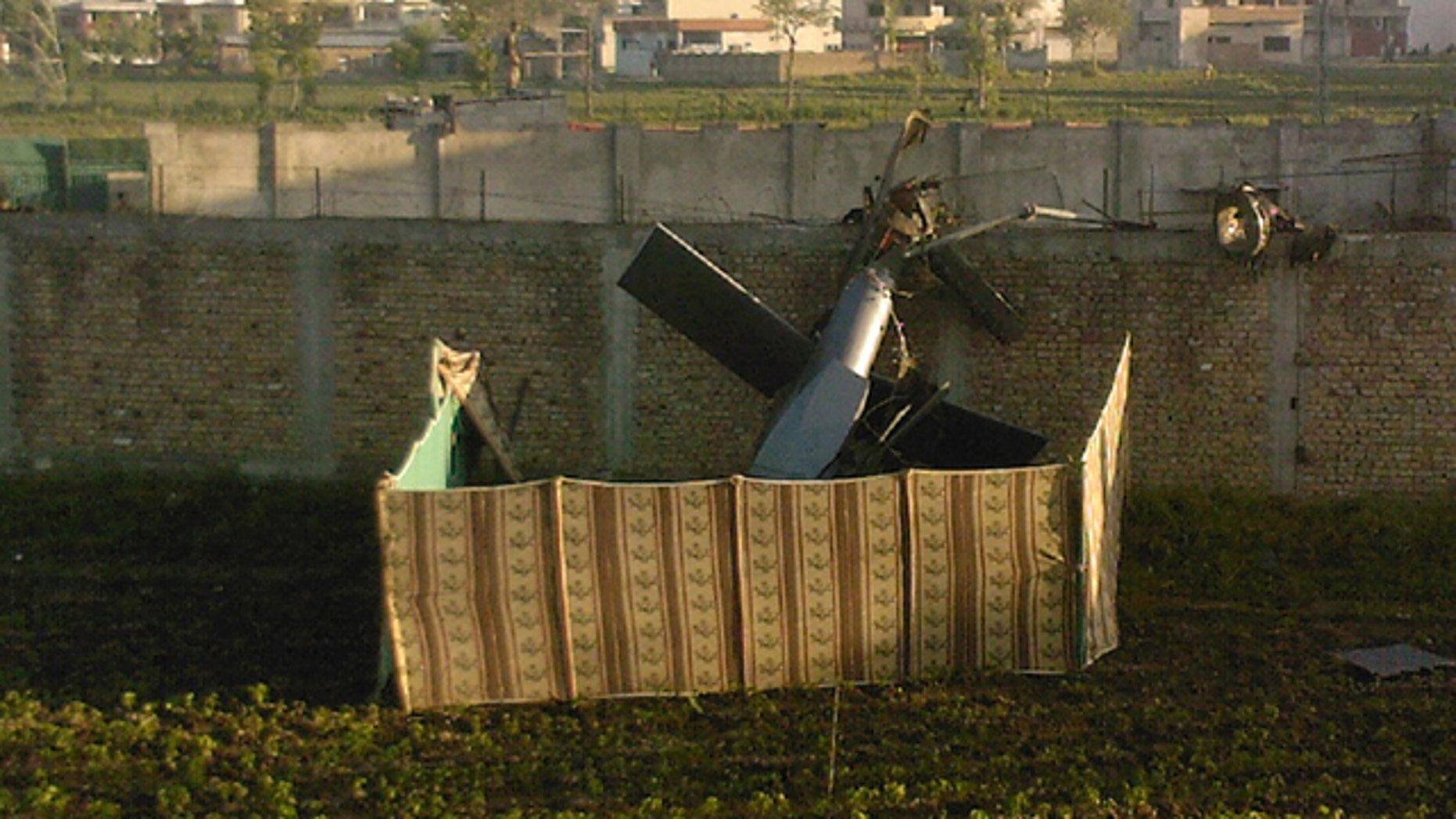 May 2: A photo taken by a local resident shows the wreckage of a helicopter next to the wall of the compound where, according to officials, Osama bin Laden was shot and killed in a firefight with U.S. forces in Abbottabad, Pakistan. Bin Laden, the glowering mastermind behind the Sept. 11, 2001, terror attacks that killed thousands of Americans, was slain in his luxury hideout in Pakistan early Monday. (AP/Mohammad Zubair)