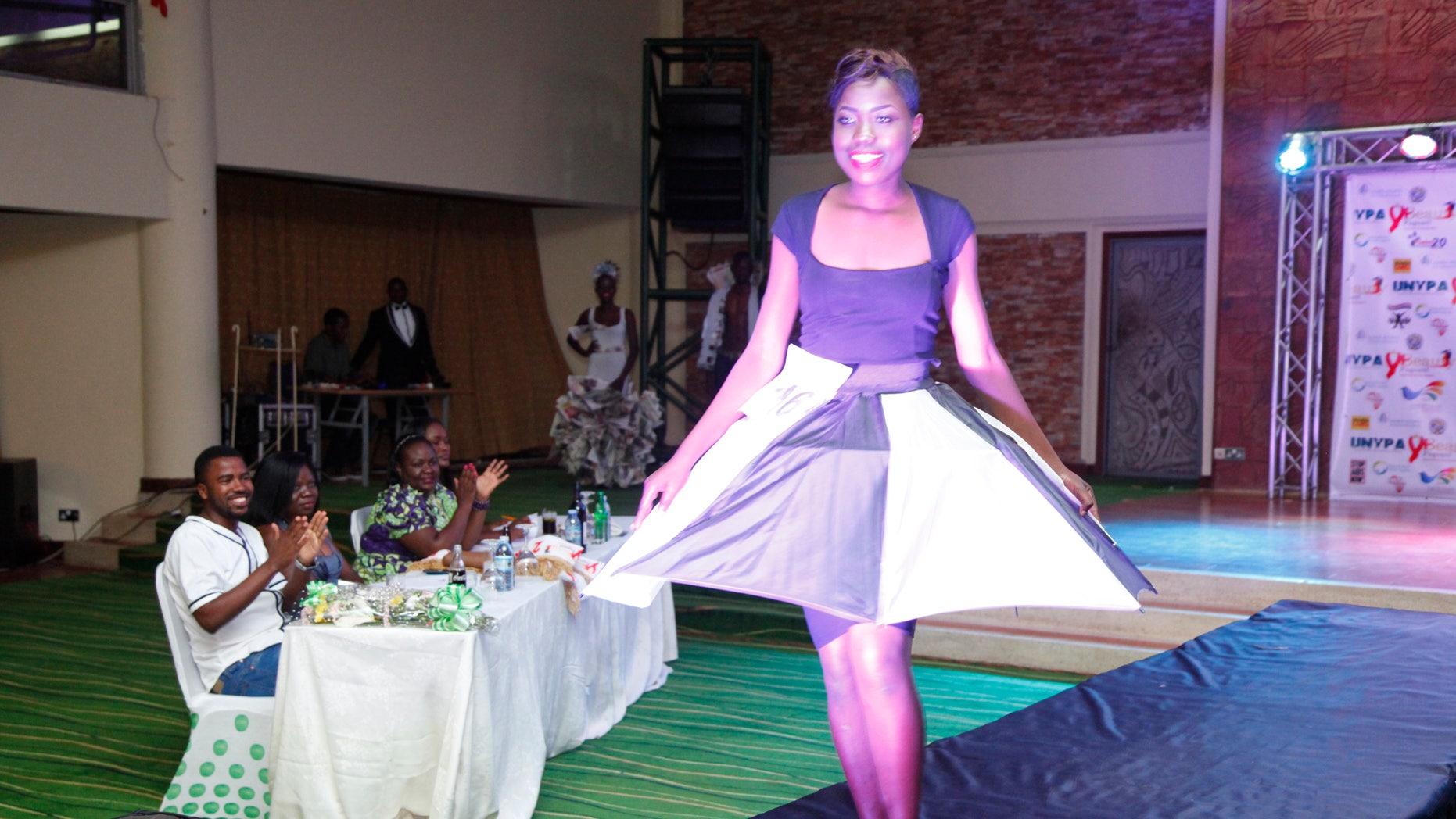 A Ugandan wearing a dress made from an umbrella on the runway at the third annual Uganda Network of Young People Living with HIV beauty pageant at Golf Course Hotel Kampala, Uganda, Saturday Sept. 24, 2016. The event aims at encouraging youth living with HIV to open up and educate fellow youths of the dangers of the disease.