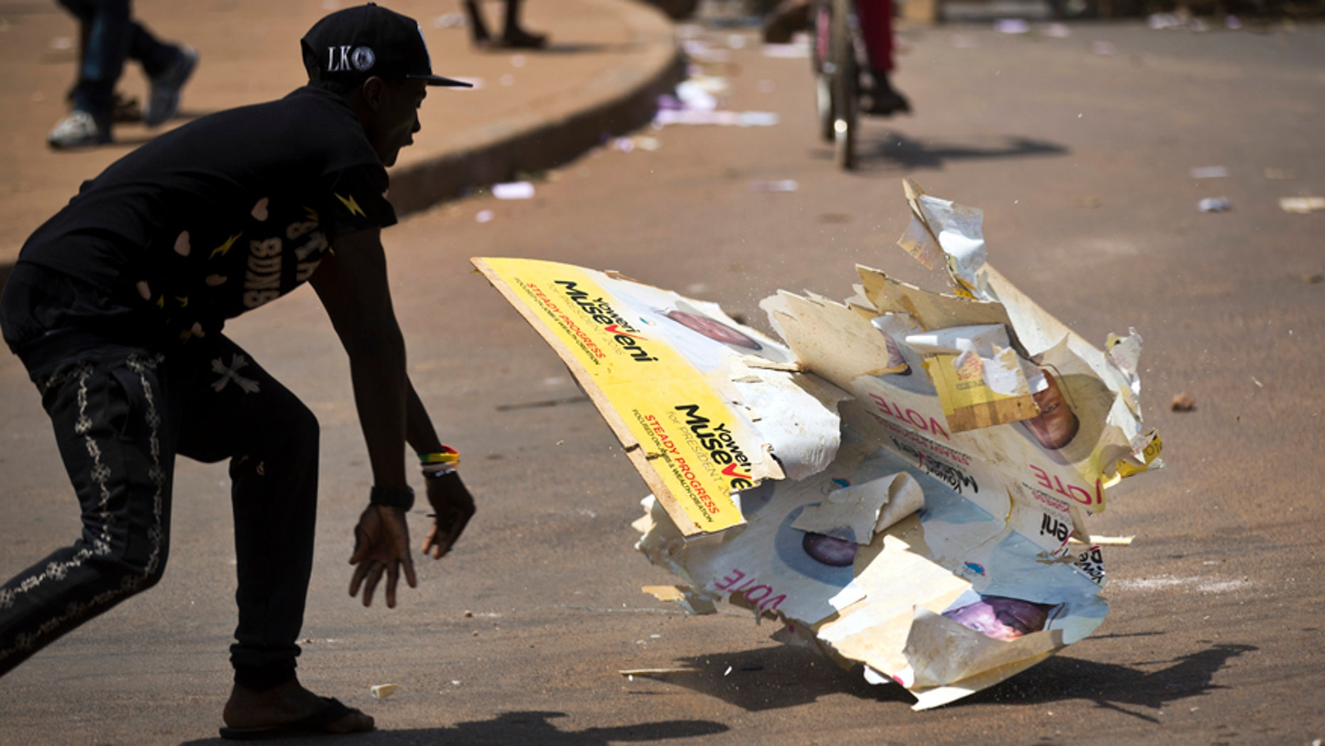 Feb. 18, 2016: An angry voter smashes a campaign placard of long-time President Yoweri Museveni, outside a polling station where voting material for the presidential election never arrived, at a polling station in Ggaba, on the outskirts of Kampala, in Uganda.