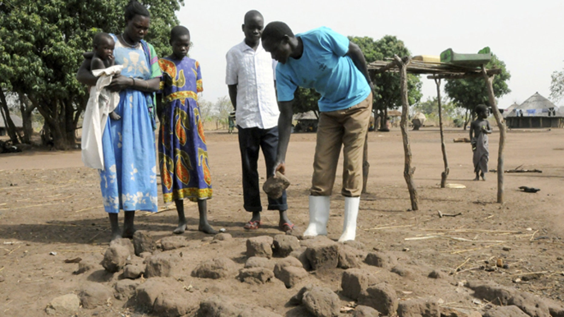 In this photo taken Monday Feb. 20, 2012, a Ugandan family shows the grave of a family member who died of nodding disease in Kitgum district, Uganda.