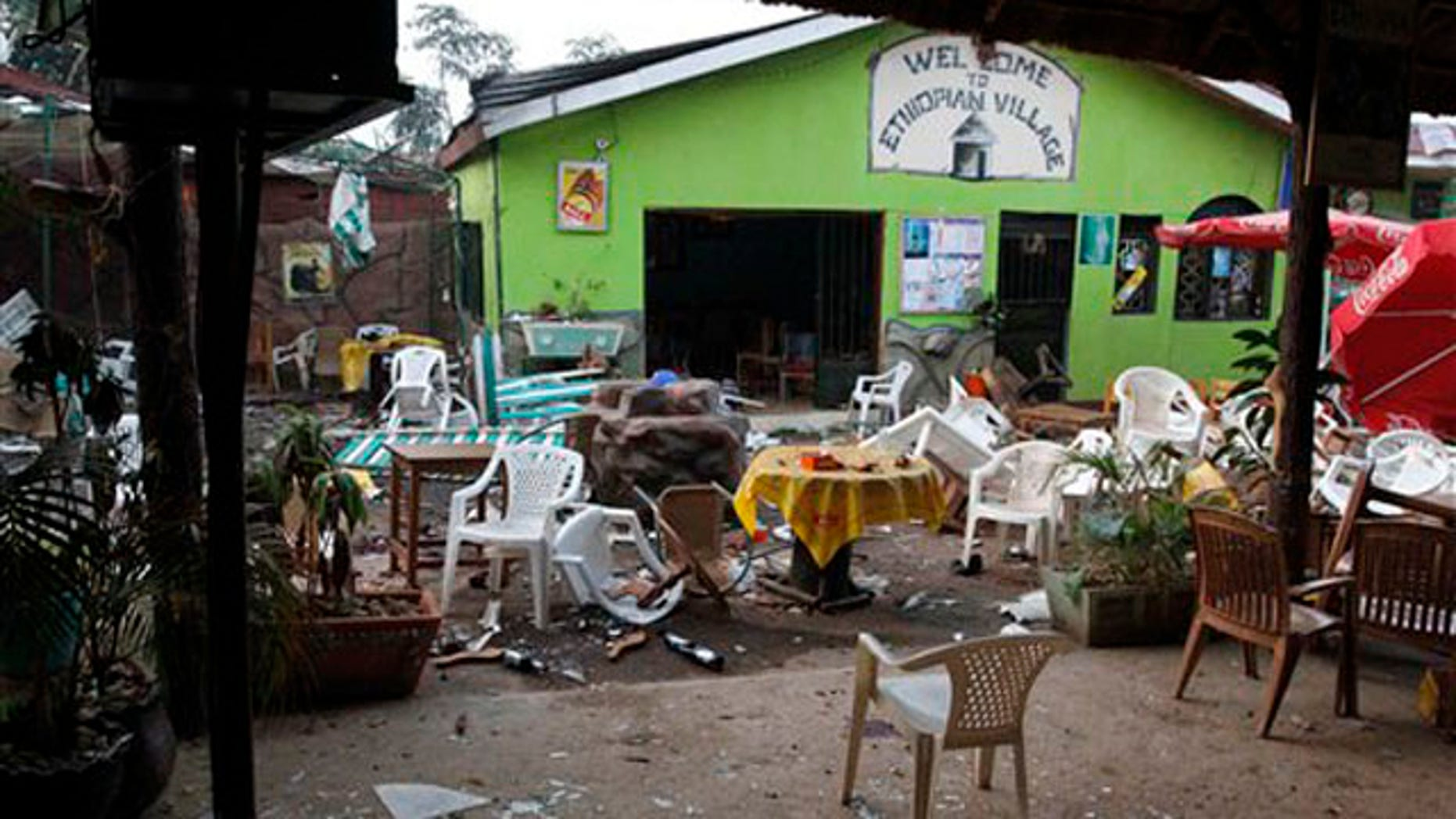 "Damaged chairs and tables are seen among the debris strewn outside the restaurant ""Ethiopian village"" in Kampala, Uganda, July 12 after an explosion at the restaurant late Sunday. (AP Photo)"