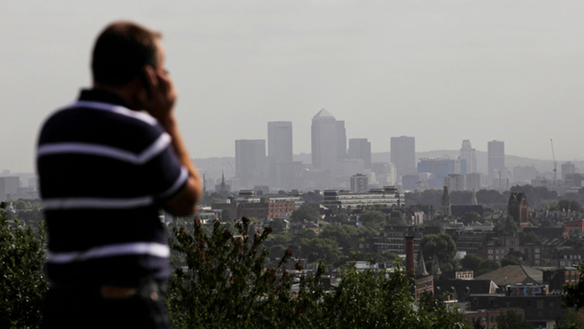FILE In this Friday, Sept. 23, 2011 file photo a man talks on a mobile phone as the hi-rise buildings of the banks based in the Canary Wharf business district are seen in the distance from Parliament Hill on Hampstead Heath in London.