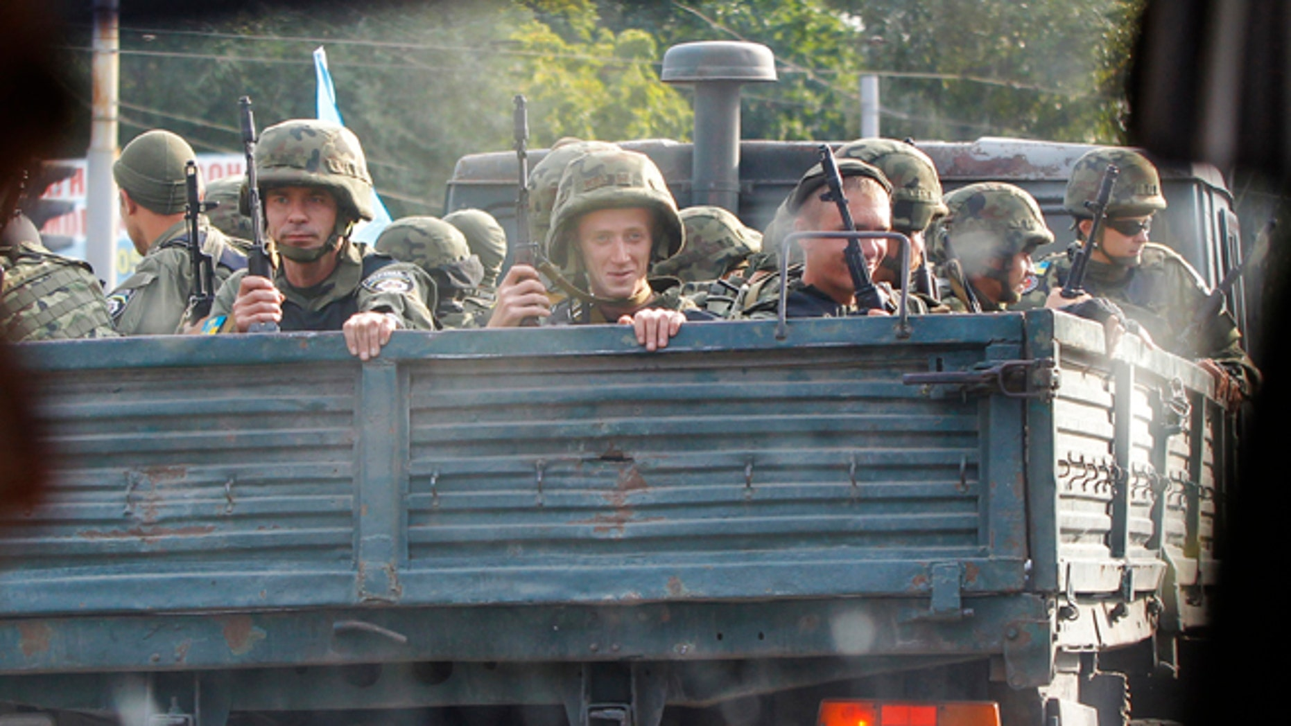 Ukrainian soldiers drive on a truck in the southern coastal town of Mariupol, Ukraine, Monday, Sept. 8, 2014. Poroshenko made a surprise trip Monday to a key city in southeastern Ukraine as a cease-fire between Russian-backed rebels and Ukrainian troops appeared to be largely holding. (AP Photo/Sergei Grits)