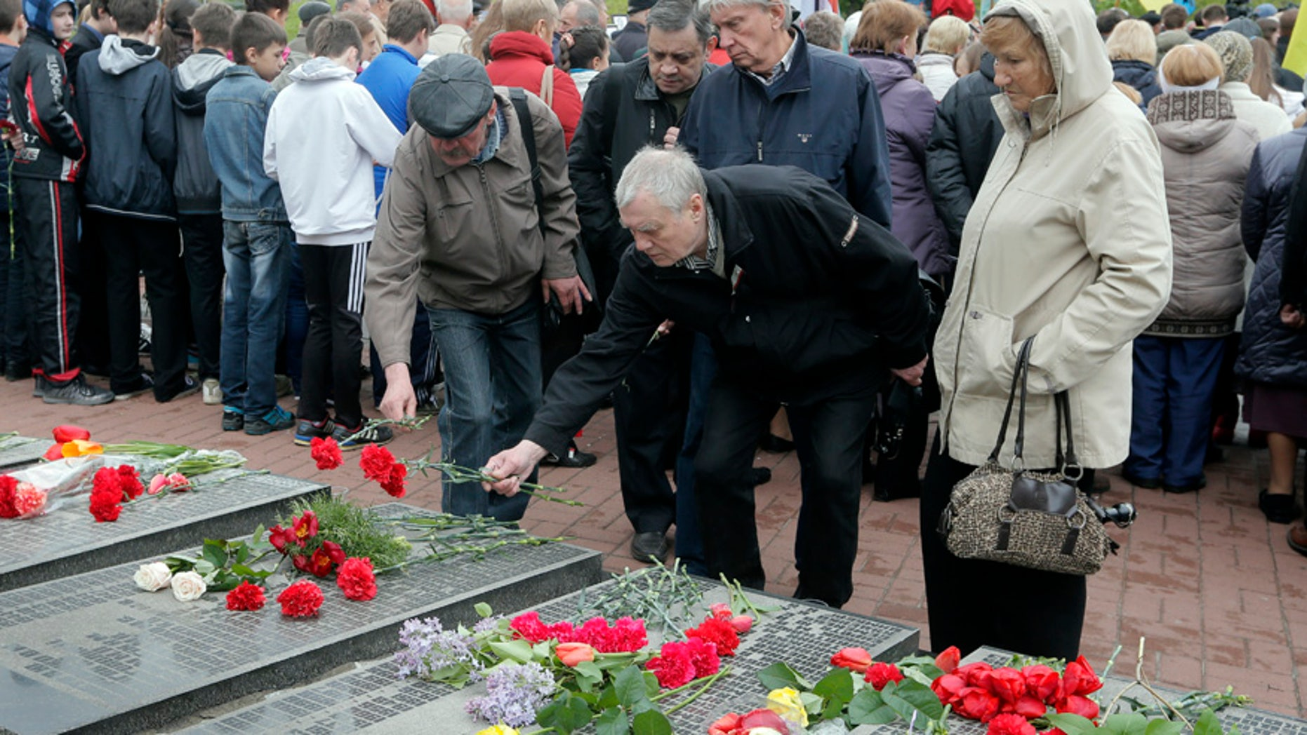 April 26, 2016: Ukrainians lay flowers to the tombstone that bears their relative's names, during a ceremony to commemorate victims of Chernobyl tragedy at a monument to them in Ukraine's capital Kiev, Ukraine.