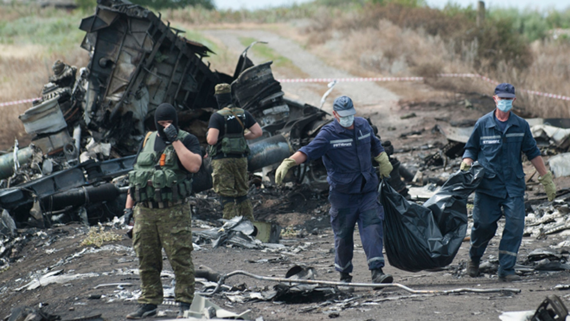 July 20, 2014: Ukrainian Emergency workers carry a stretcher with a victim's body in a bag as pro-Russian fighters stand in guard at the crash site of Malaysia Airlines Flight 17 near the village of Hrabove, eastern Ukraine.