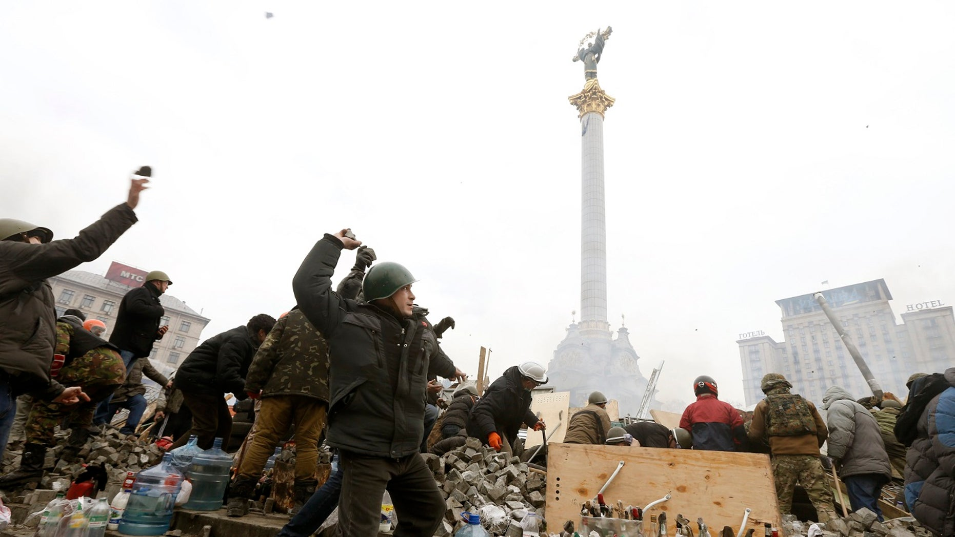 Anti-government protesters throw stones toward Interior Ministry members and riot police in Independence Square in central Kiev, Feb. 19, 2014.