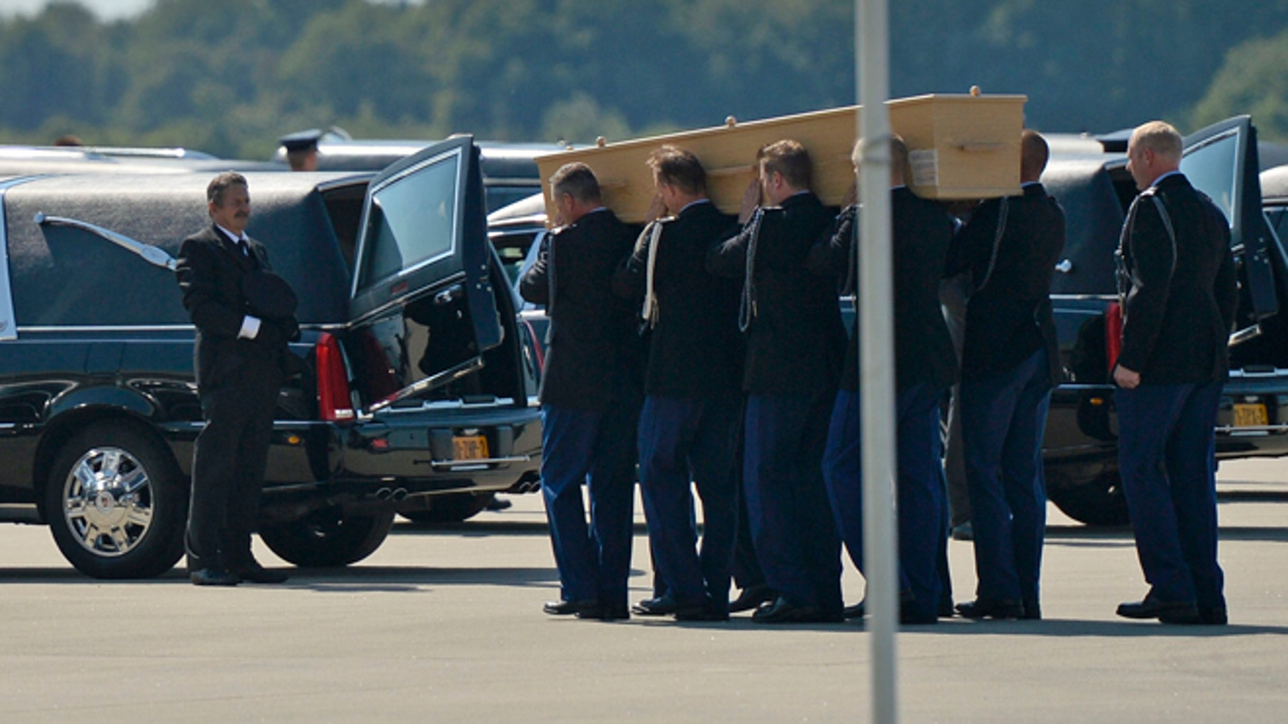 July 23, 2014: Soldiers load coffins into cars under a Ukrainian flag during a ceremony to mark the return of the first bodies, of passengers and crew killed in the downing of Malaysia Airlines Flight 17, from Ukraine at Eindhoven military air base.