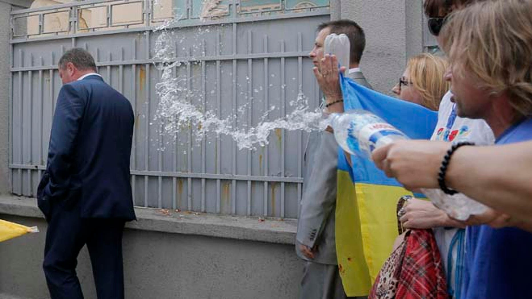 In this Tuesday, Aug. 12, 2014 file photo, activists throw water at various lawmakers as they demonstrate to demand sanctions against Russia, during a protest opposite the parliament building in Kiev, Ukraine.