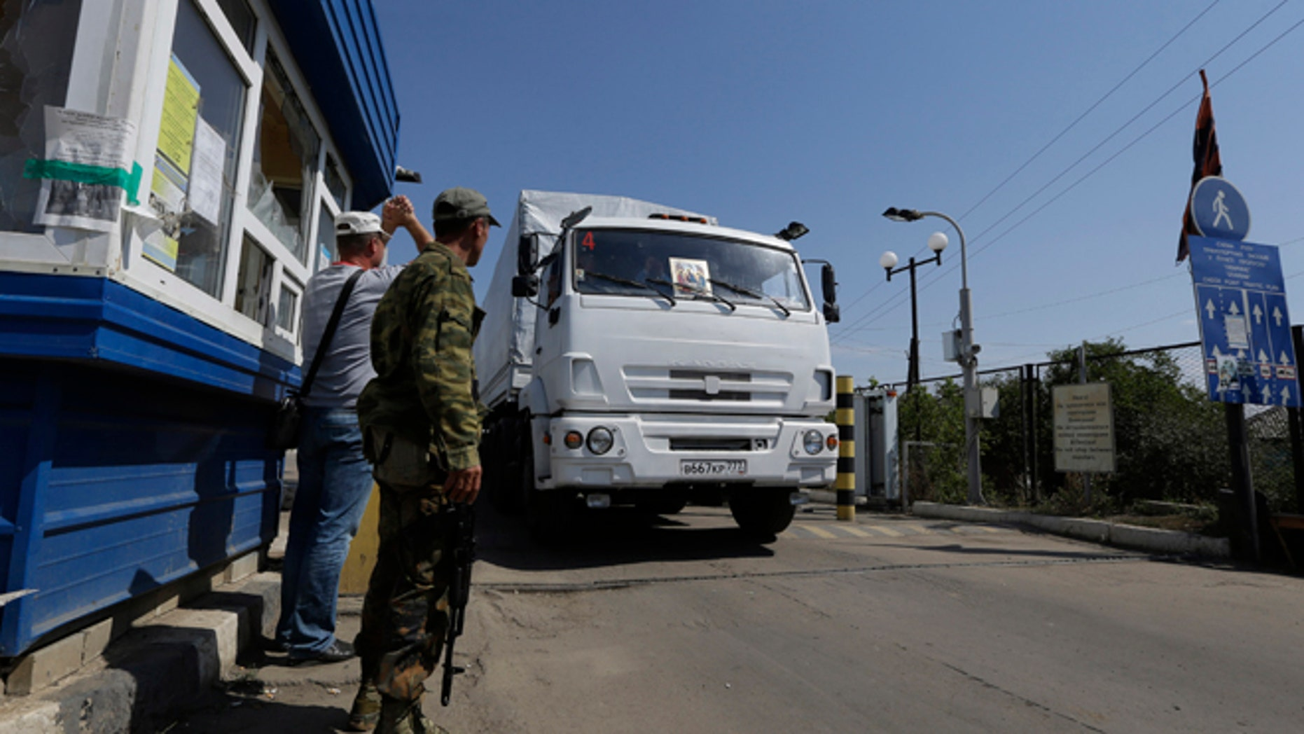 Aug. 22, 2014: Ukrainian border guards look at the first aid truck as it passes the border post at Izvaryne, eastern Ukraine. (AP/Sergei Grits)