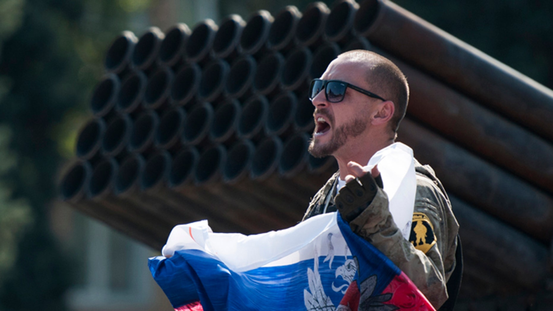 Aug. 24, 2014: A pro-Russian rebel holds a Russian national flag near to damaged heavy hardware from the Ukrainian army during an exhibition in the central square in Donetsk, eastern Ukraine. (AP/Antoine E.R. Delaunay)