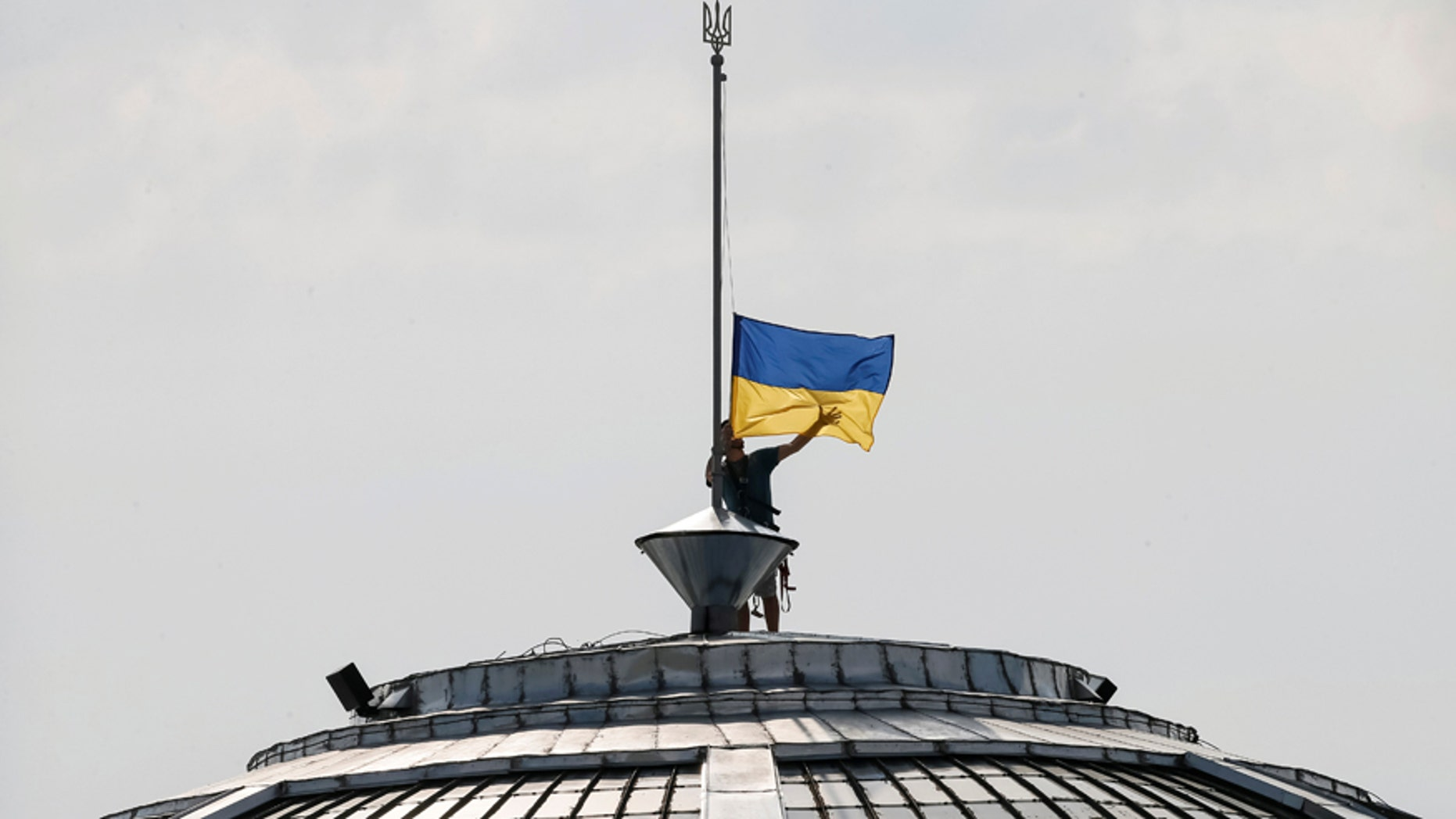 File photo - A climber installs the Ukrainian national flag on a roof, marking the Day of the State Flag, on the eve of the Independence Day, in Kiev, Ukraine, Aug. 23, 2016. (REUTERS/Gleb Garanich)