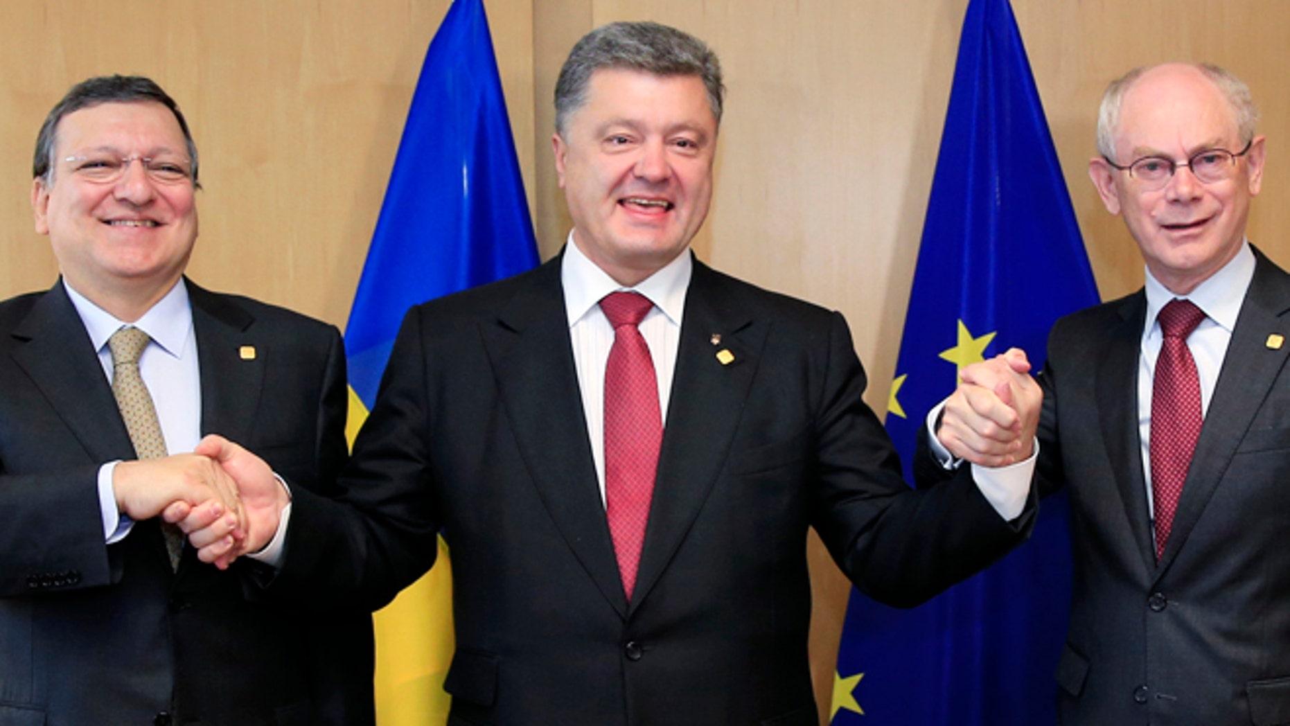 June 27, 2014: Ukraine's President Petro Poroshenko poses with European Commission President Jose Manuel Barroso (L) and European Council President Herman Van Rompuy (R) at the EU Council in Brussels.