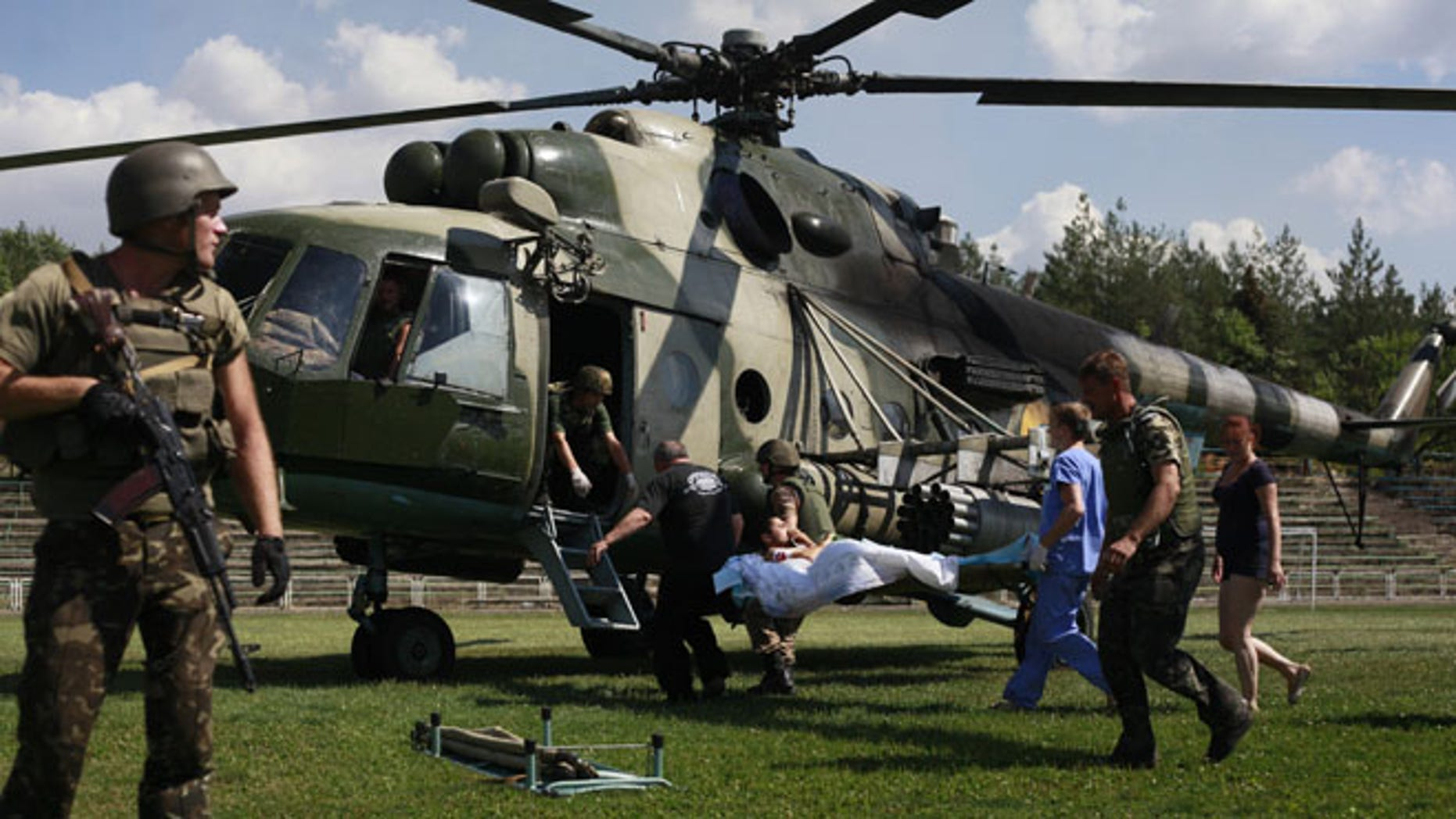 Ukrainian soldiers evacuate a wounded comrade close to Luhansk, eastern Ukraine, Thursday, Aug. 21, 2014.  The rebel stronghold 20 kilometers from the Russian border has been under siege for 19 days, lacking basic amenities like running water or electricity. (AP Photo/Petro Zadorozhnyy)