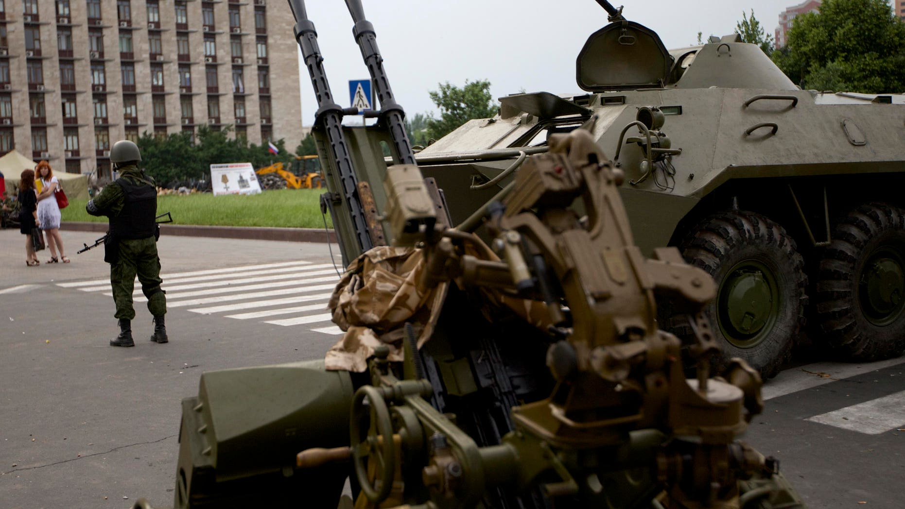 May 29, 2014: A Pro-Russian militia member guards next to an APC and anti-aircraft gun, outside the administrational building in Donetsk, Ukraine.