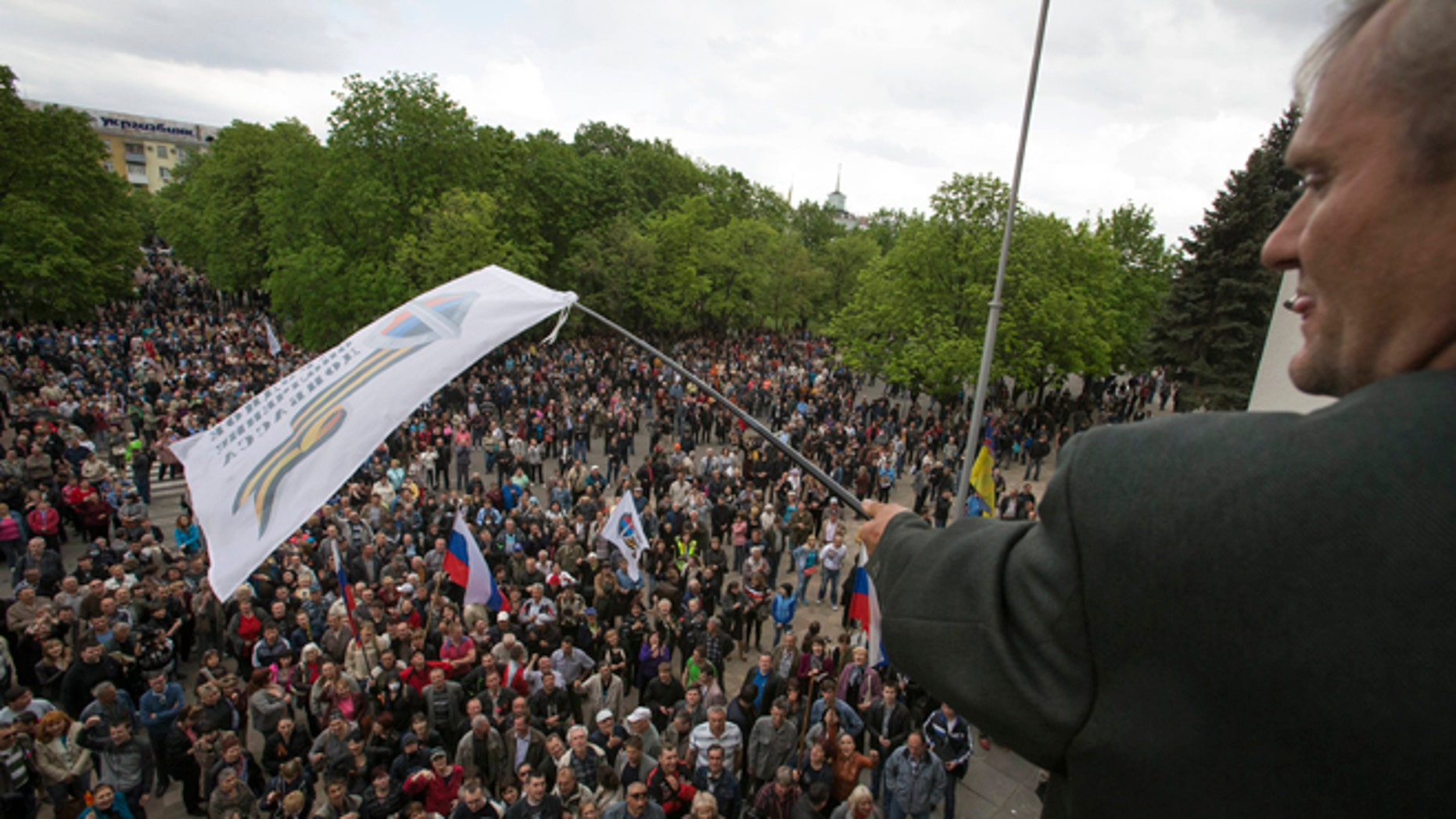 April 29, 2014: A Pro-Russian activist waves a Donbas Republic flag over a crowd celebrating the capture of an administration building in the center of Luhansk, Ukraine, one of the largest cities in Ukraine's troubled east, as demonstrators demand greater autonomy for Ukraine's regions.