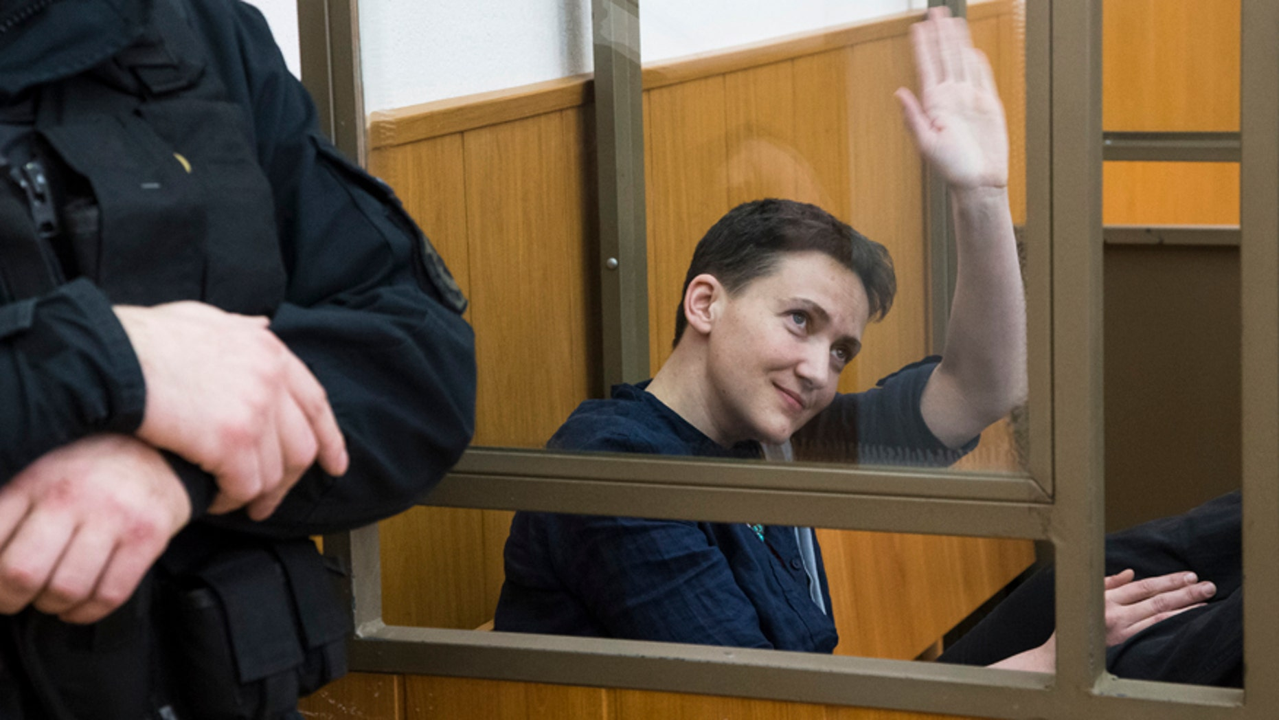 March 22, 2016: Ukrainian pilot Nadezhda Savchenko waves to journalists from a glass cage inside court, in the town of Donetsk, Rostov-on-Don region, Russia.