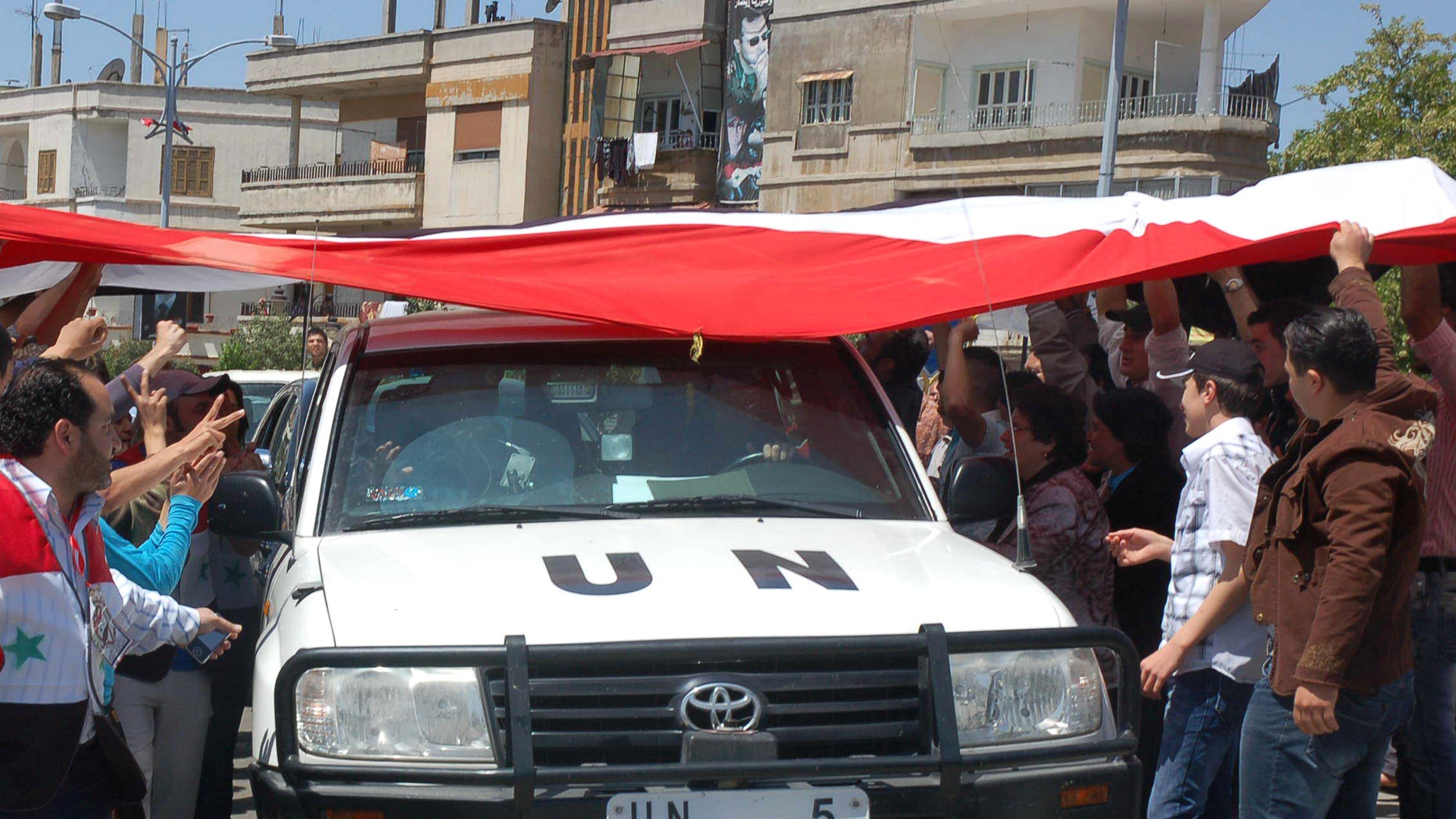 April 23: In this photo released by the Syrian official news agency SANA, a UN observers vehicle passes under a huge Syrian flag held by Syrian President Bashar Assad supporters during their visit to the pro-Syrian regime neighborhoods, in Homs province, central Syria.