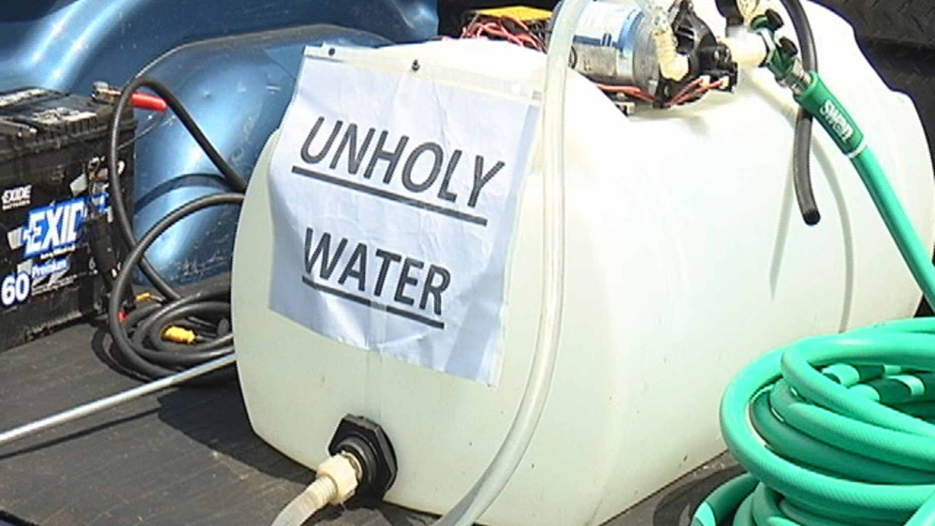 A group of athiests used 'unholy water' to wash away a religious group's blessing at the entryway to Polk County.