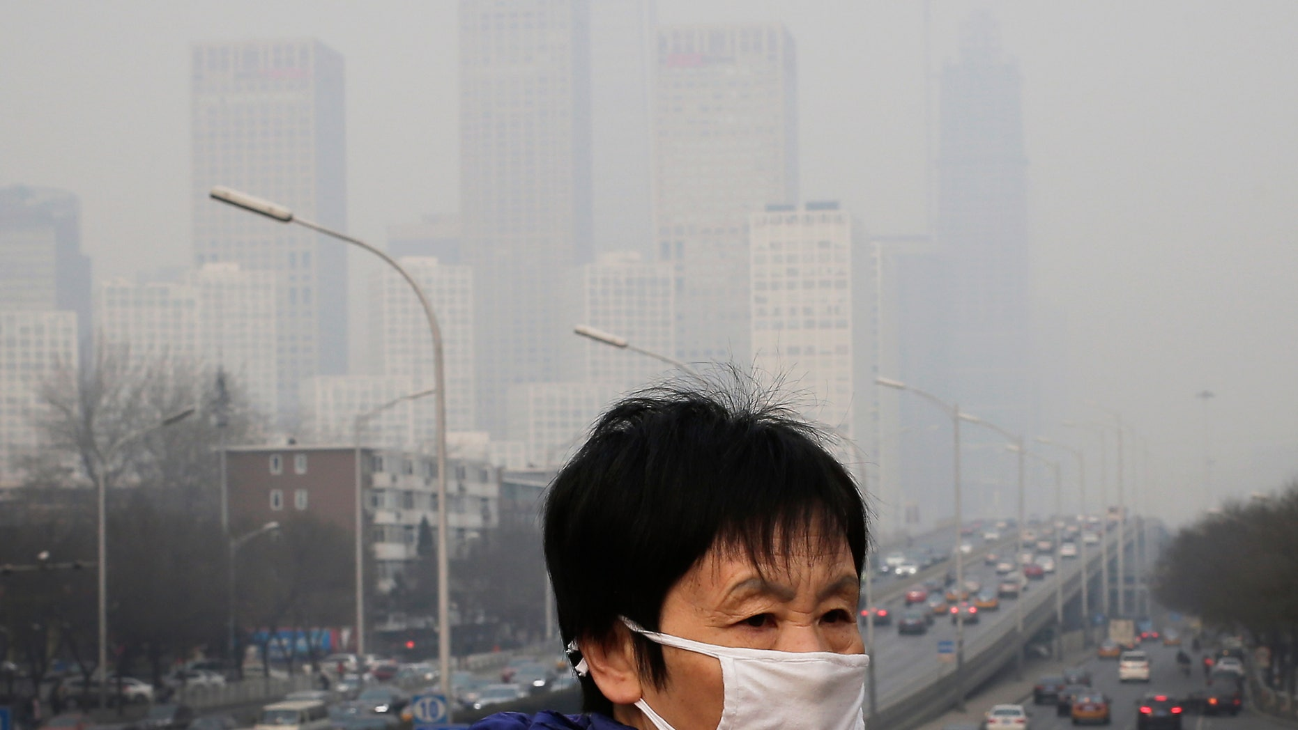 In this Dec. 20, 2015 file photo, a woman wearing a mask for protection against pollution walks on a pedestrian overhead bridge as office buildings are shrouded with smog in Beijing.