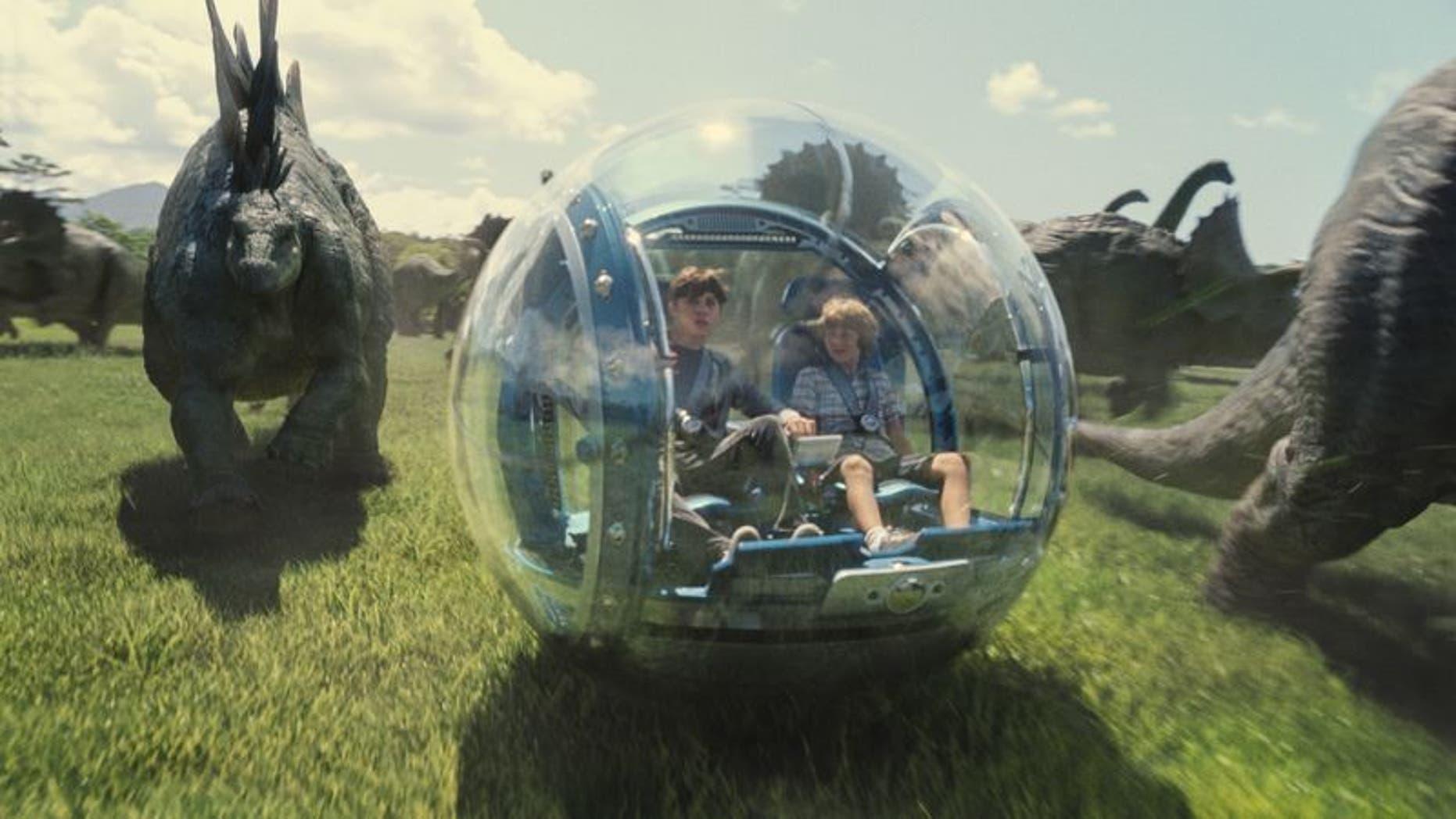 'Jurassic World' park visitors ride alongside dinosaurs in glass spheres.