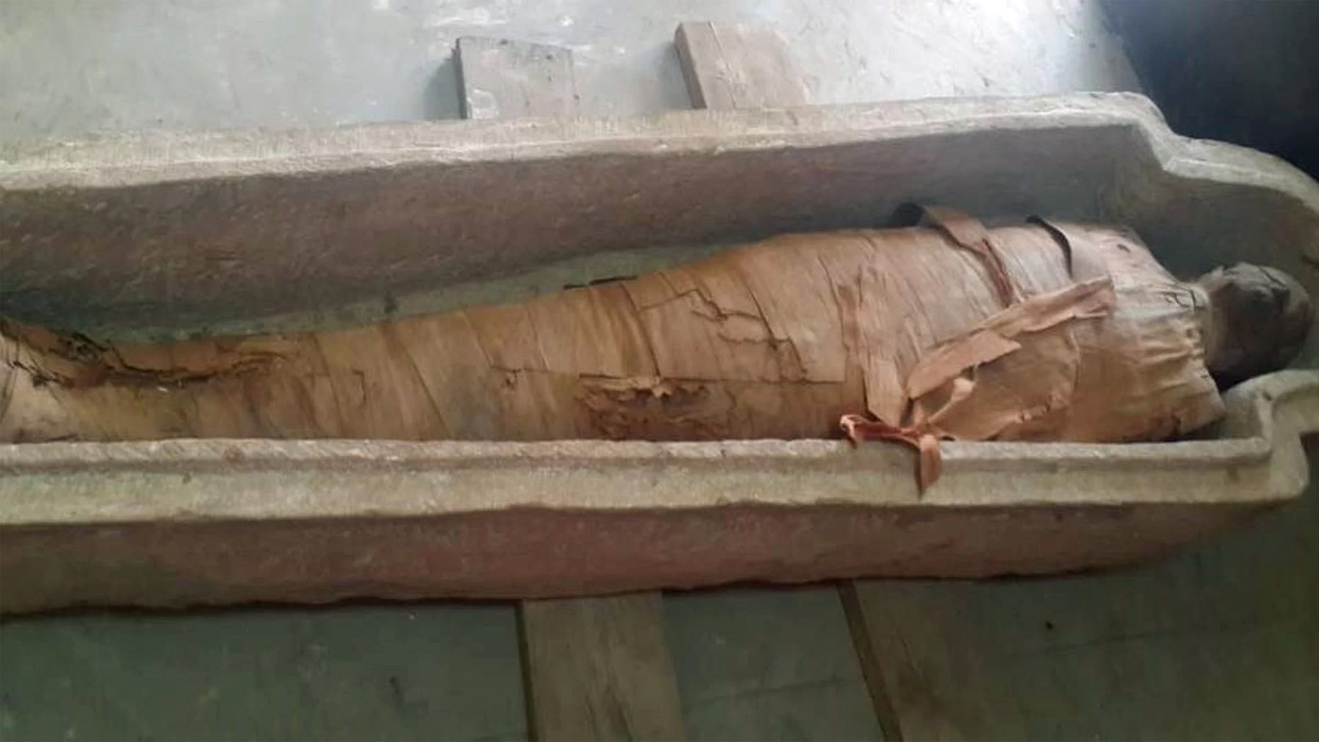 This well-preserved mummy, wrapped in linen bandages, was found inside a sandstone sarcophagus in a 2,500-year-old tomb at Aswan, in southern Egypt. The identity of the mummy is unclear. Credit: Photo courtesy of the Egyptian Ministry of Antiquities