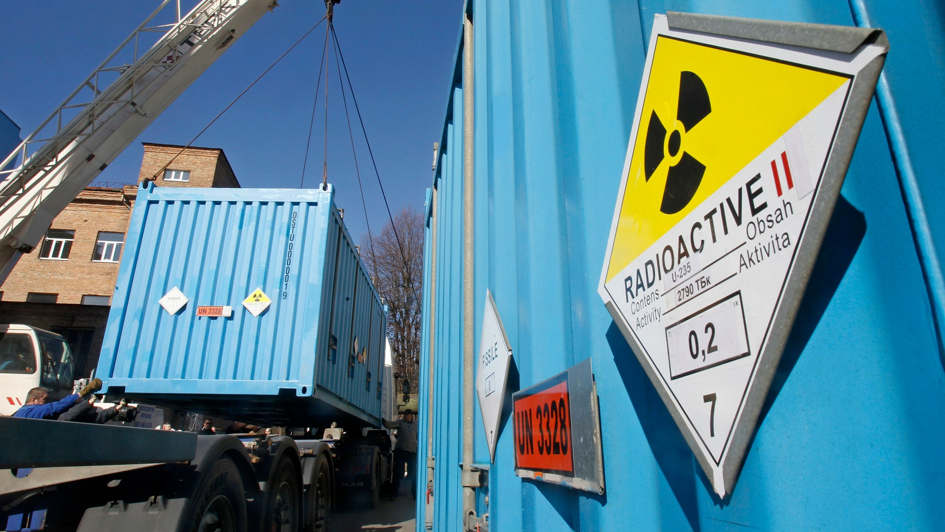 File photo - Workers place a container with spent highly-enriched uranium on a truck at a nuclear research facility in Kiev March 24, 2012. (REUTERS/Gleb Garanich)