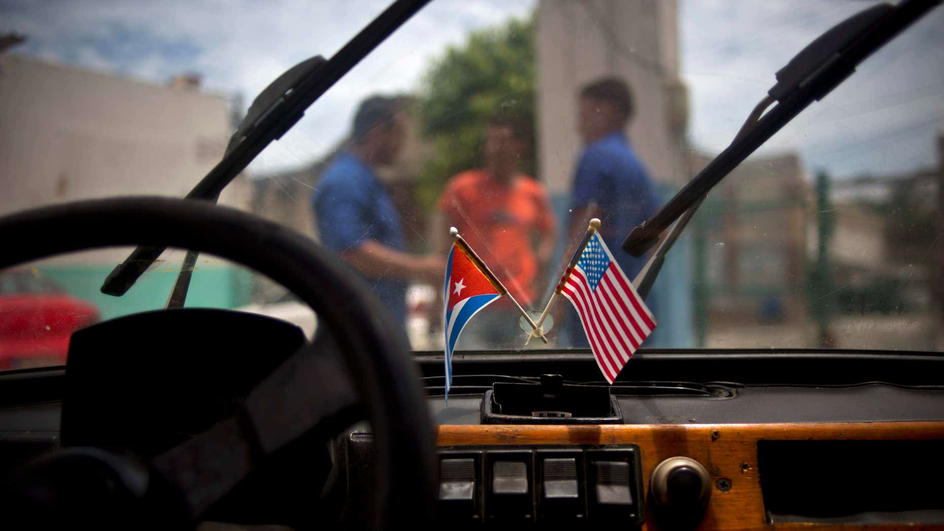 Aug. 10, 2016: A Cuban and a U.S. flag hang on the windshield of a car in a garage in Havana, Cuba.
