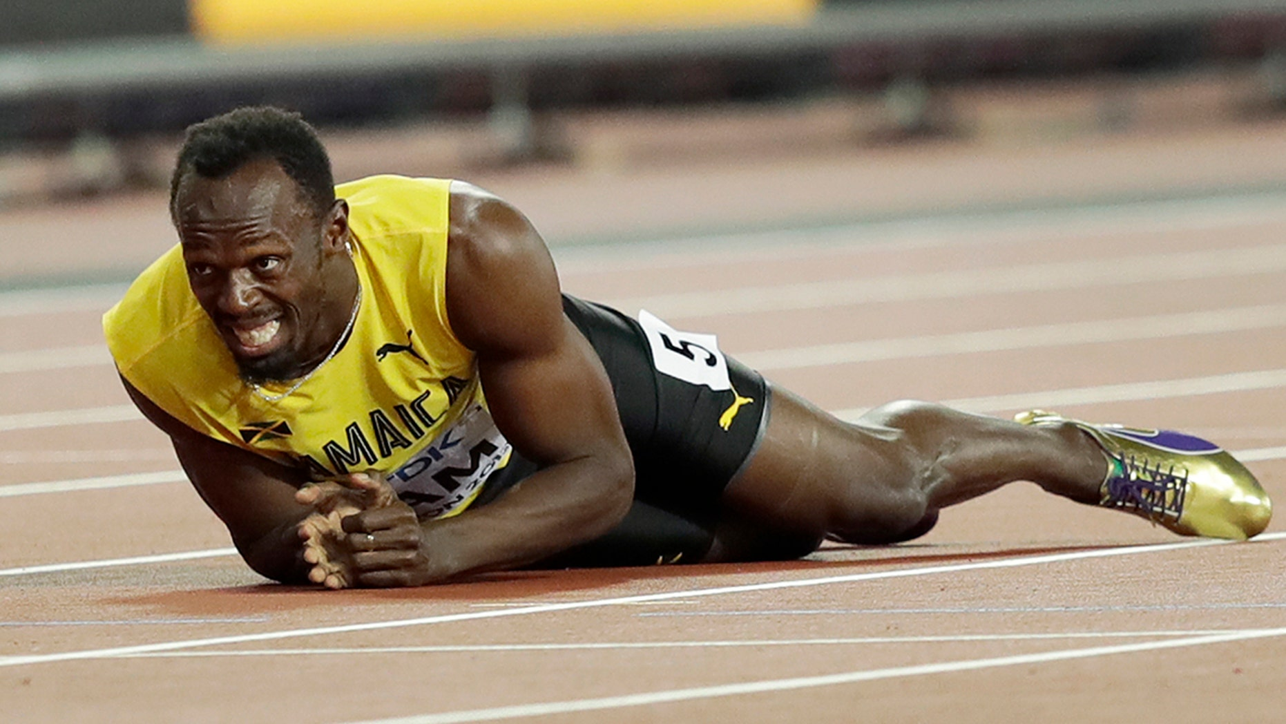 Jamaica's Usain Bolt lies on the track after he injured himself during the 4x100 m relay final during the World Athletics Championships in London Saturday.