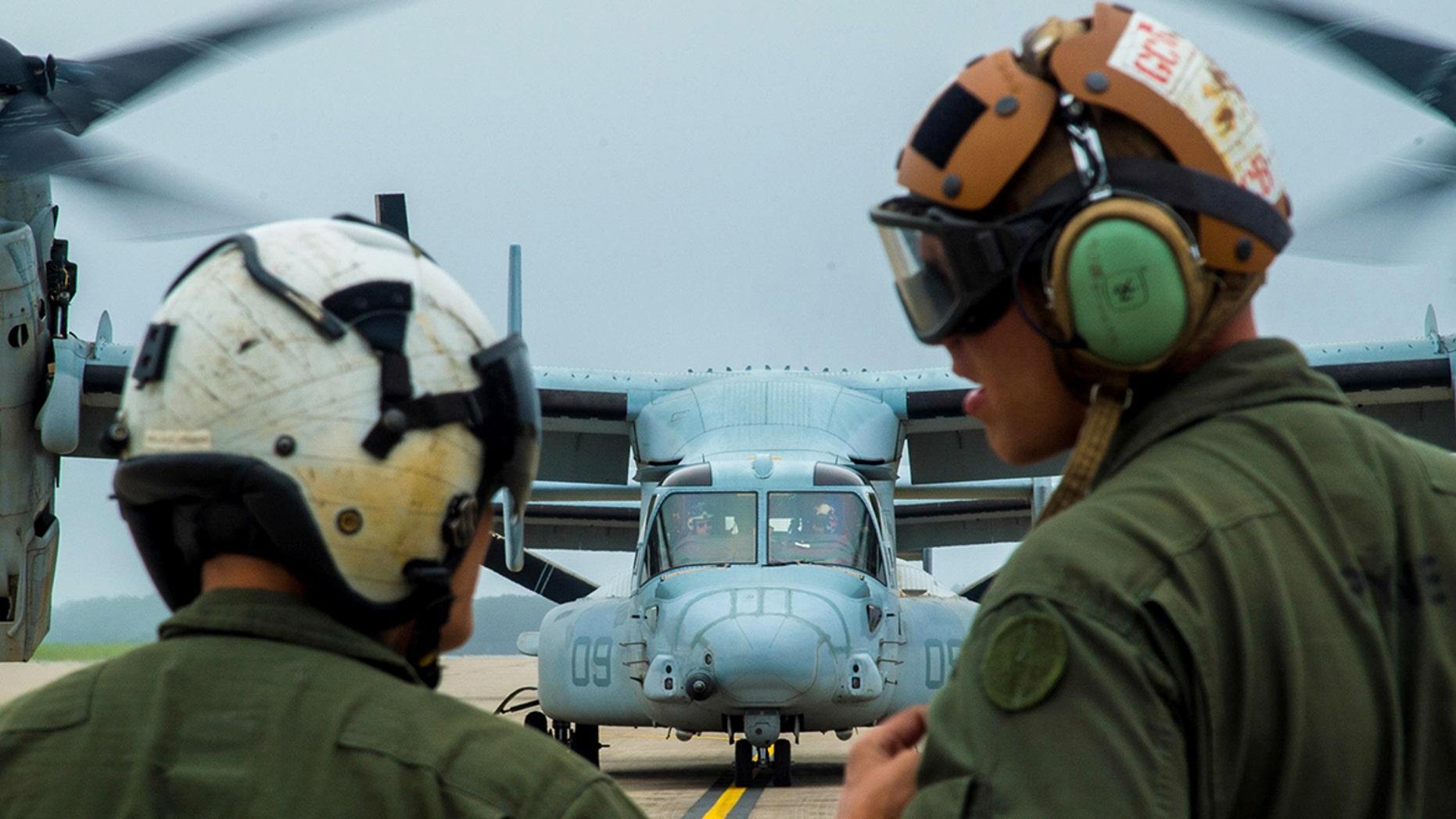 U.S. Marine Corps Cpl. Brandon Guico, a Marine Medium Tiltrotor Squadron 262 airframe aerial observer, and William Payne, a VMM-262 avionics technician, watch a MV-22 Osprey takeoff at Misawa Air Base, Japan last month.