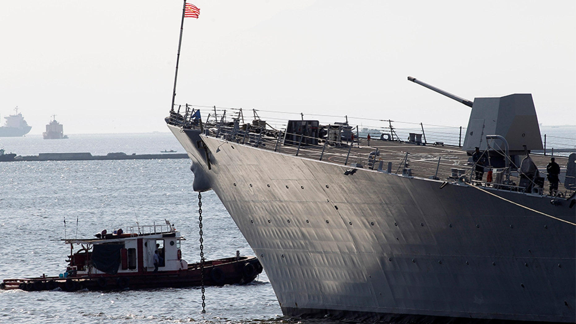 Feb. 7, 2014: A tugboat passes by the USS Pinckney in Manila.