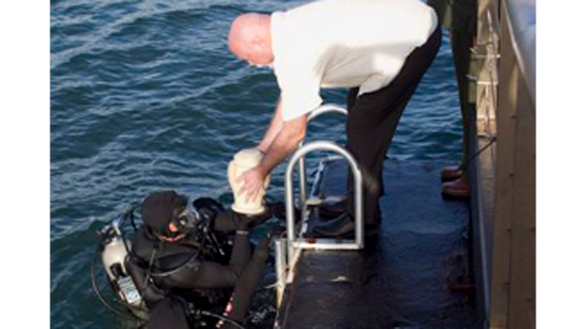 Dec. 23, 2011: As National Parks Historian Daniel Martinez salutes, Jerry Cabiness, center, hands the remains of his father to divers to be interred inside the USS Arizona in Honolulu.