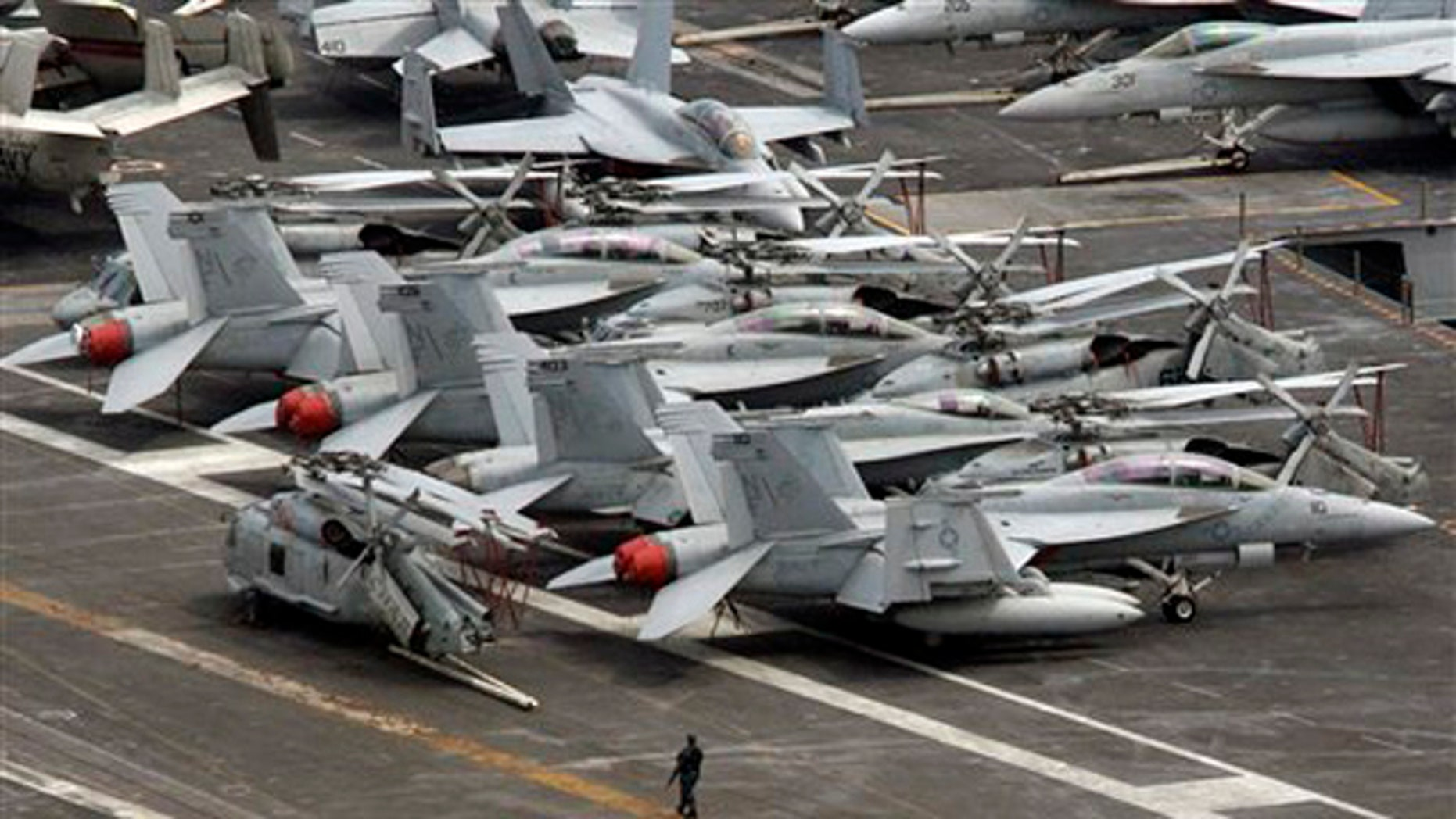 July 24, 2010: An armed military personnel stands near a flight line on the deck of U.S. nuclear-powered aircraft carrier USS George Washington at the Busan port in Busan, south of Seoul, South Korea.