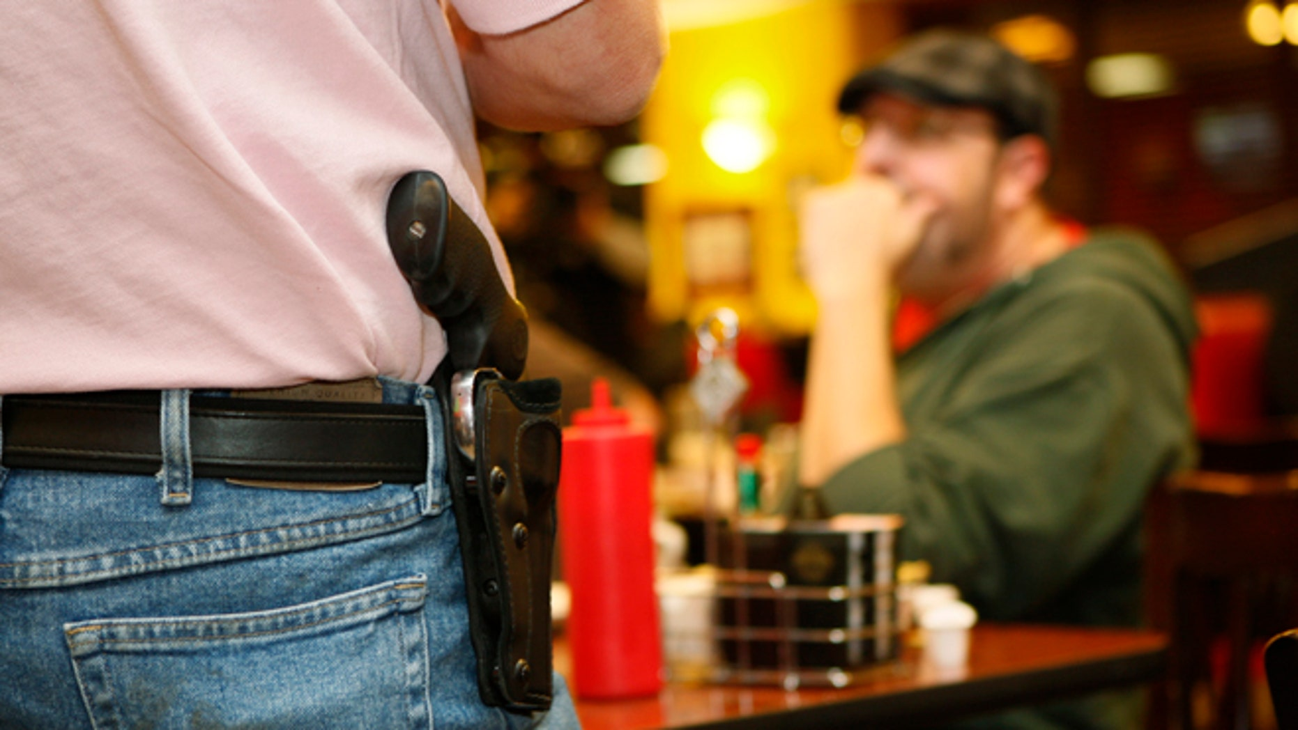 FILE: Nov. 1, 2012: A Oklahoma resident wears an unconcealed side arm at Beverly's Pancake House in Oklahoma City, Okla., a state that passed a concealed-carry law last year.