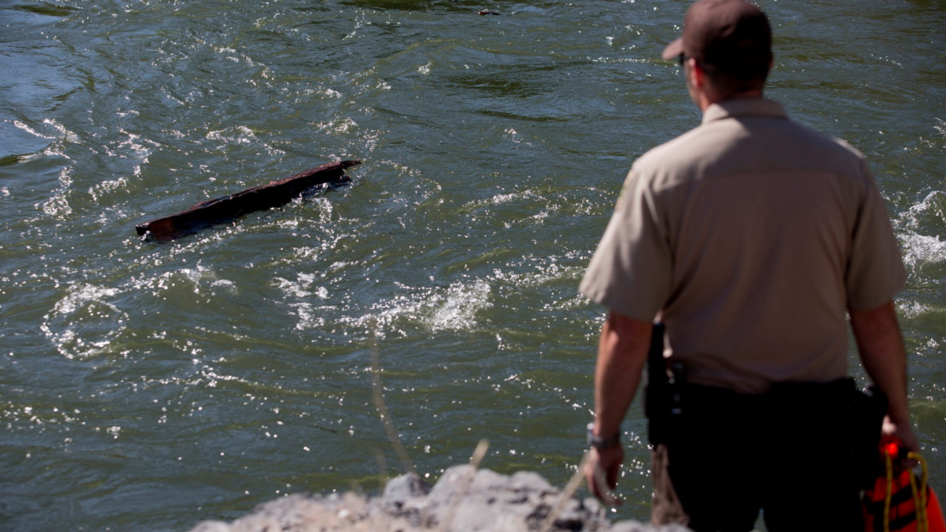 In this Monday, May 29, 2017 photo, police, fire and search and rescue officials respond to a scene along the Provo River near Provo, Utah.
