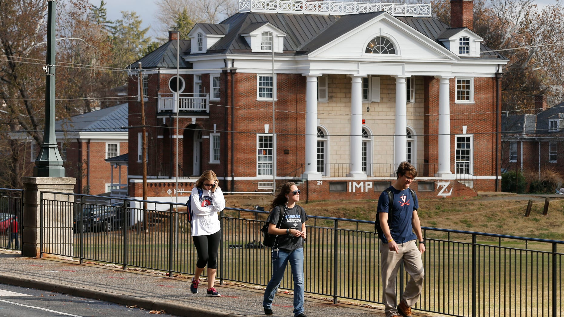 Nov. 24, 2014: University of Virginia students walk to campus past the Phi Kappa Psi fraternity house at the University of Virginia