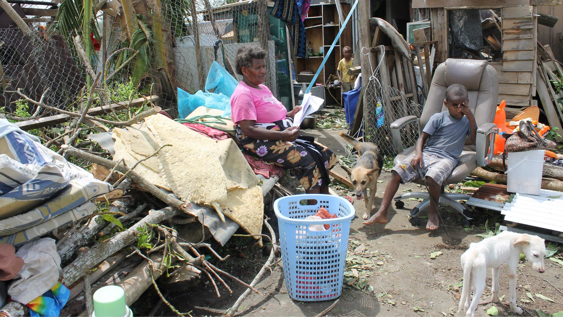 March 17, 2015: Family in the Nikinini community sits surrounded by their belongings in the aftermath of Cyclone Pam.