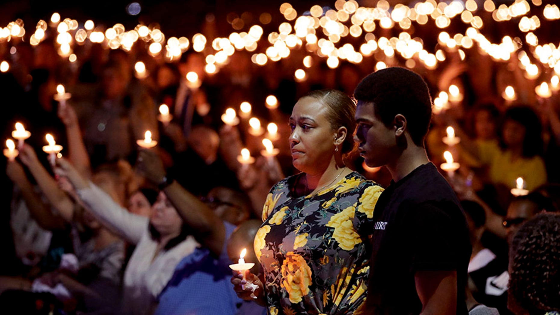 Oct. 5, 2017: Veronica Hartfield, stands with her son, Ayzayah Hartfield during a candlelight vigil for her husband, Las Vegas police officer Charleston Hartfield.