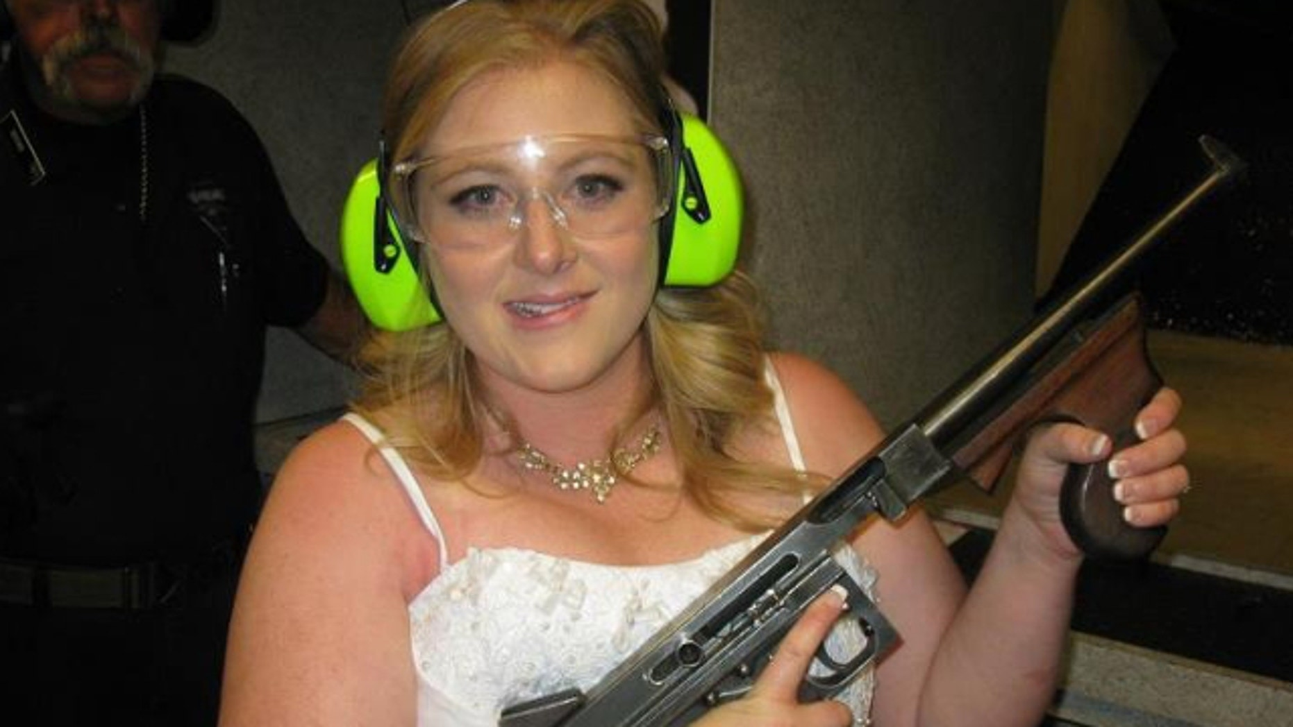 """July 28, 2012: Lindsae MacDuff holds an automatic weapon at the Gun store in Las Vegas after her """"shotgun wedding."""""""