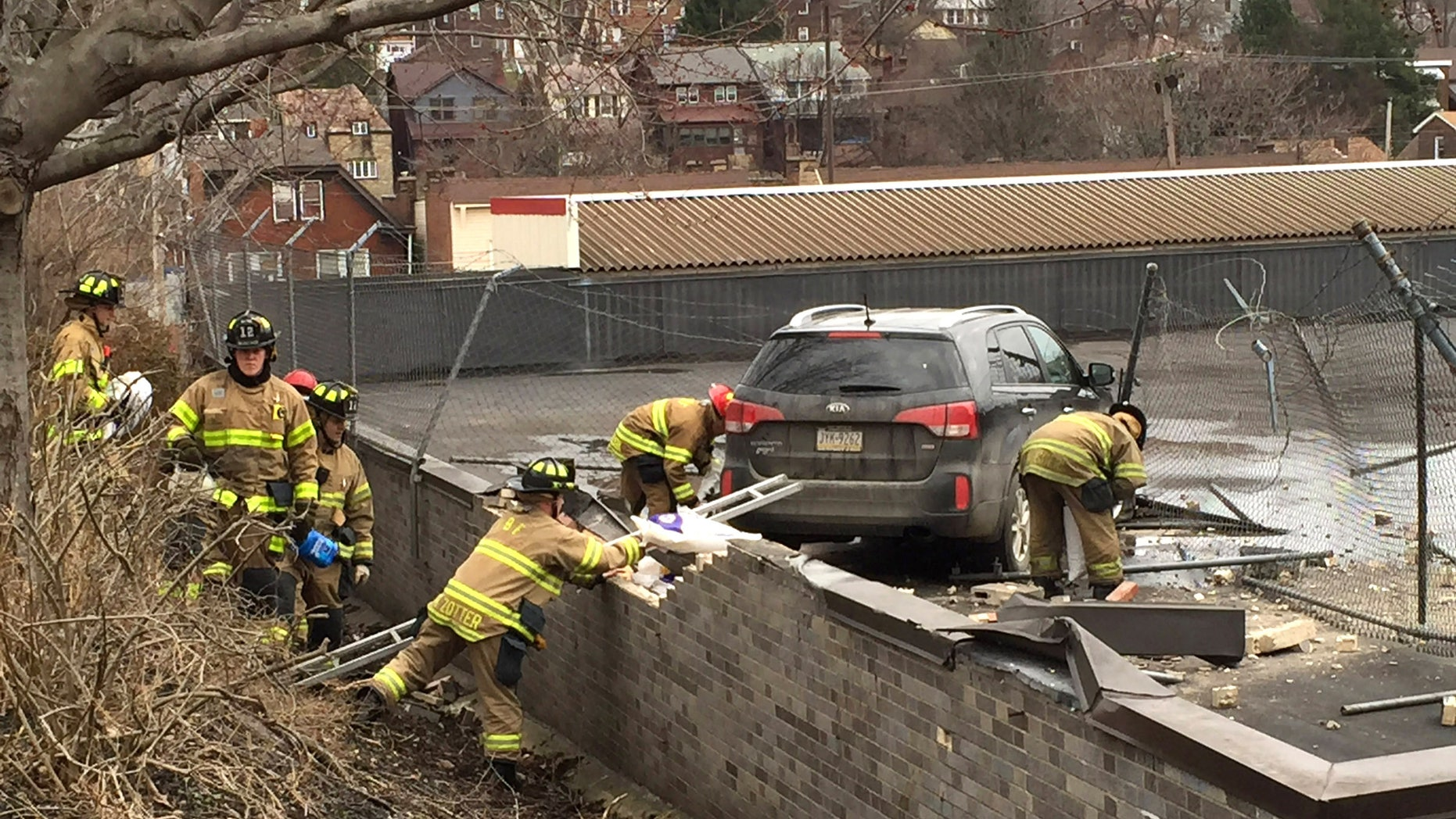 Emergency personnel check a vehicle that crashed onto the roof of a supermarket.