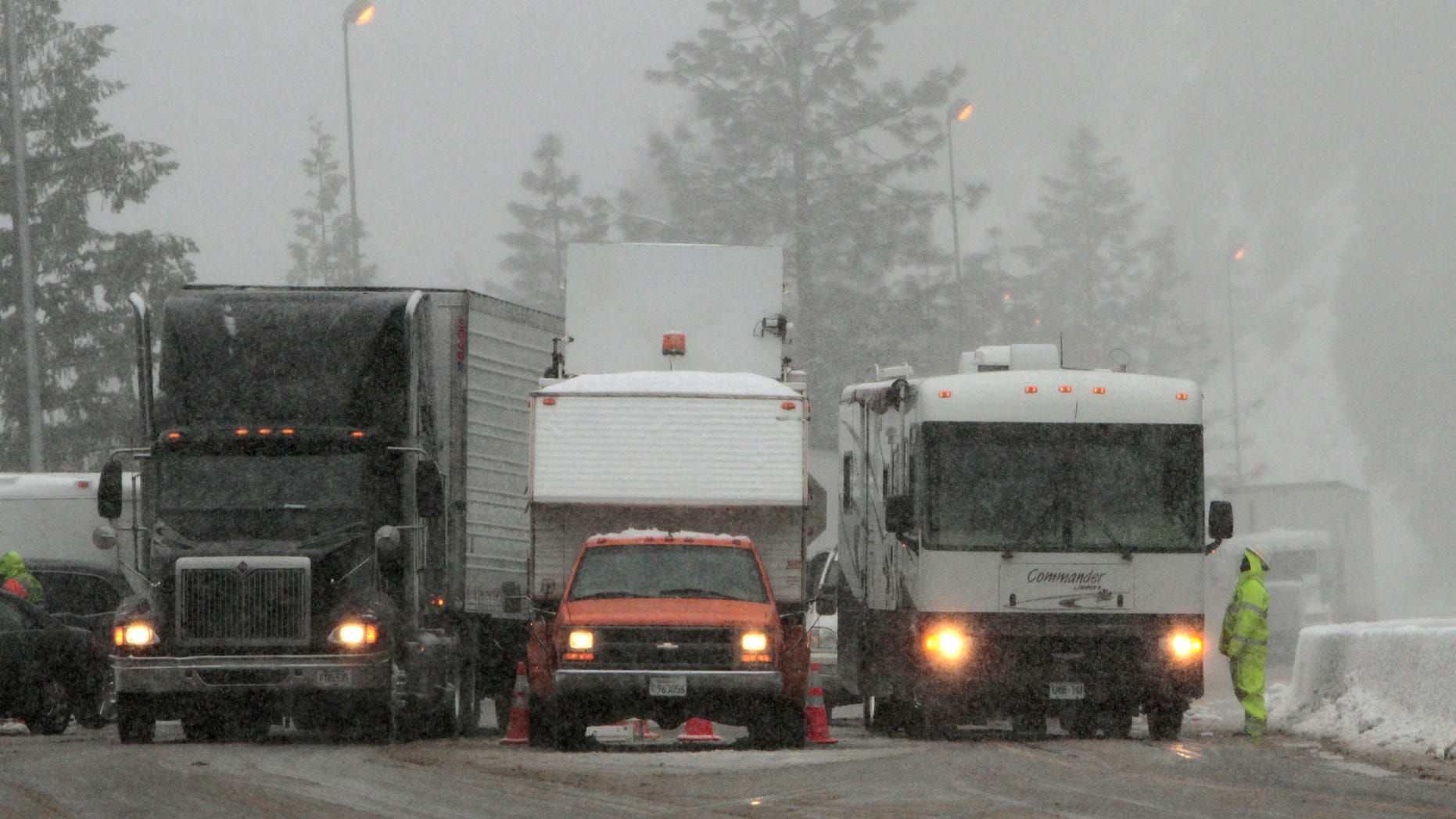 Vehicles pass through a California Departement of Transportation chain inspection stop on eastbound Interstate 80 near Alta, Calif., Thursday March 24, 2011. (AP)