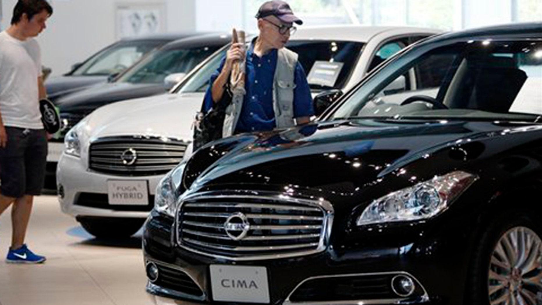 FILE: July 26, 2012: Visitors inspect cars at the Nissan Motor Co. global headquarters in Yokohama, Japan.